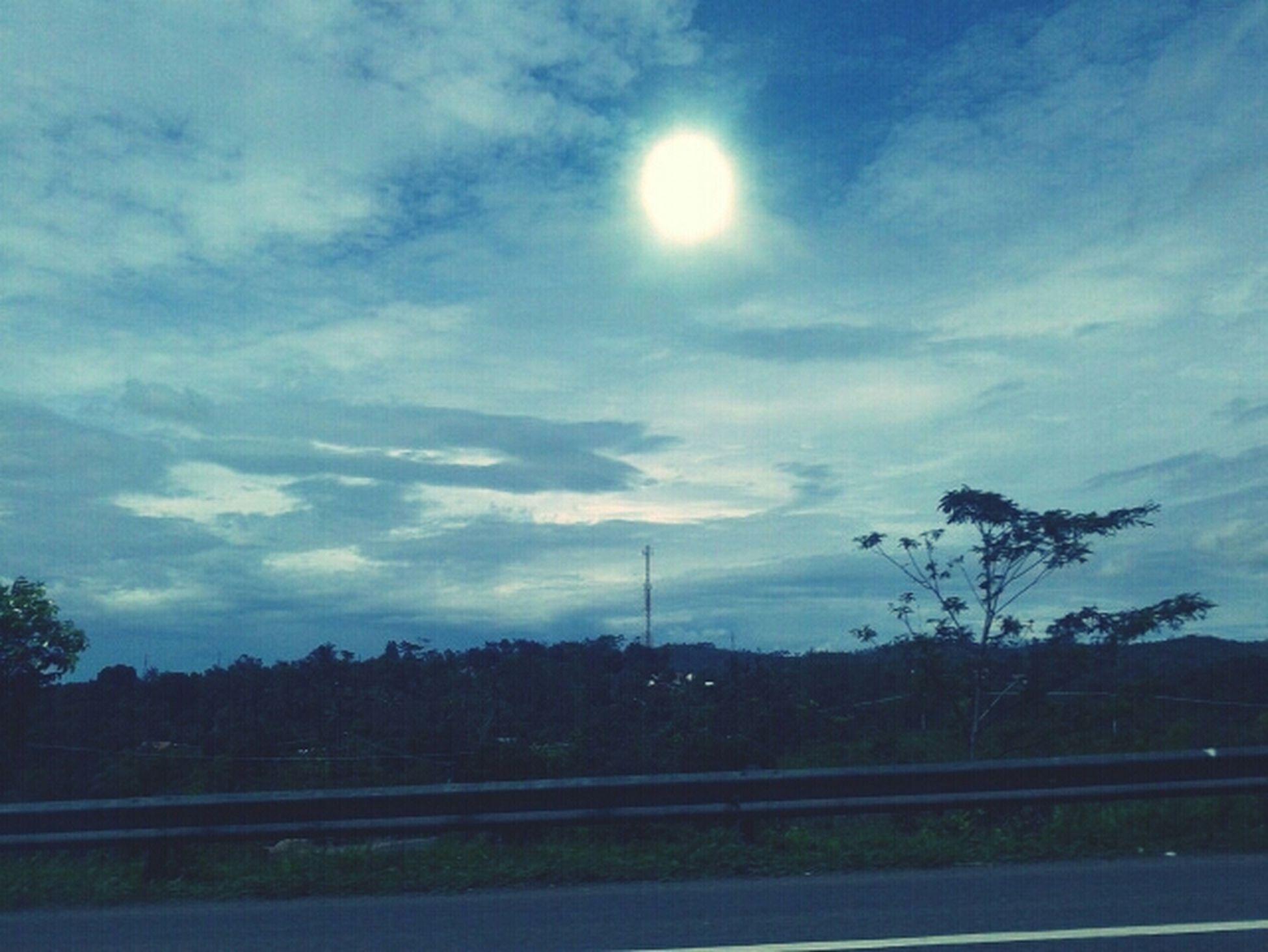 sky, tree, cloud - sky, tranquility, sun, silhouette, tranquil scene, nature, road, scenics, beauty in nature, sunlight, landscape, cloud, electricity pylon, field, power line, cloudy, sunbeam, transportation