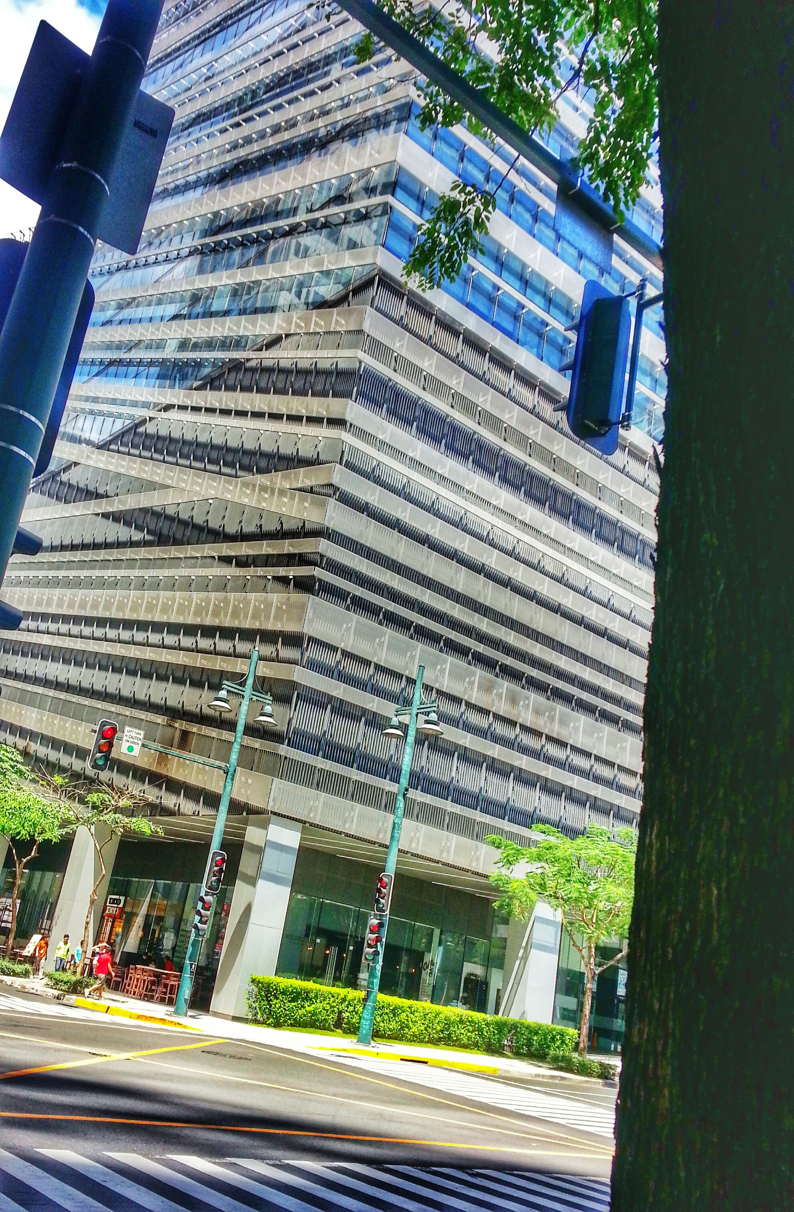 architecture, building exterior, built structure, city, modern, skyscraper, office building, building, tower, tall - high, city life, street, low angle view, incidental people, car, day, transportation, outdoors, residential building, sky