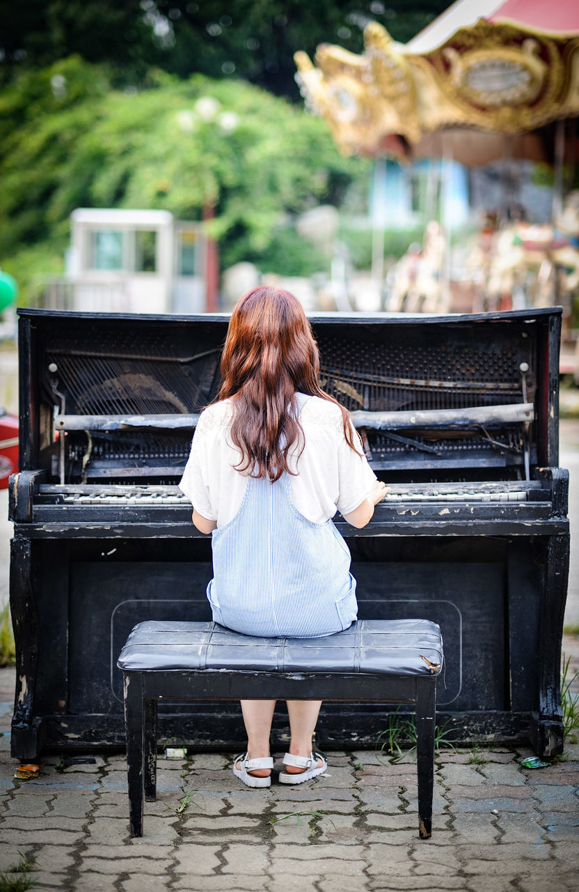 piano, rear view, real people, music, one person, redhead, musical instrument, sitting, full length, playing, day, leisure activity, lifestyles, women, pianist, young adult, outdoors, musician, architecture, young women, people