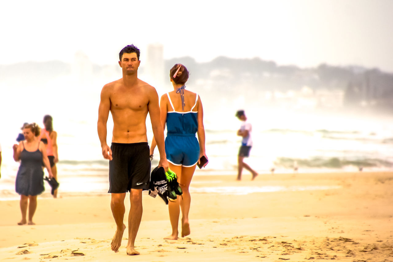 beach, shirtless, real people, sea, sand, vacations, sky, focus on foreground, lifestyles, nature, leisure activity, sunlight, beauty in nature, water, outdoors, men, togetherness, full length, standing, friendship, day, people