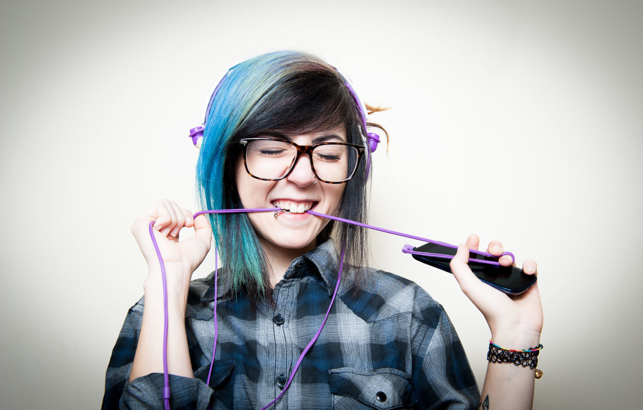 Young pretty teen woman happy listening music with smartphone and earphones Alternative Blue Hair Cheerful Earphones Eyeglasses  Front View Girl Happy Holding Hypster Indoors  Listening Music Listening One Person Portable Information Device Portrait Preety Real People Smartphone Studio Shot Teen Teenager Woman Young Young Women
