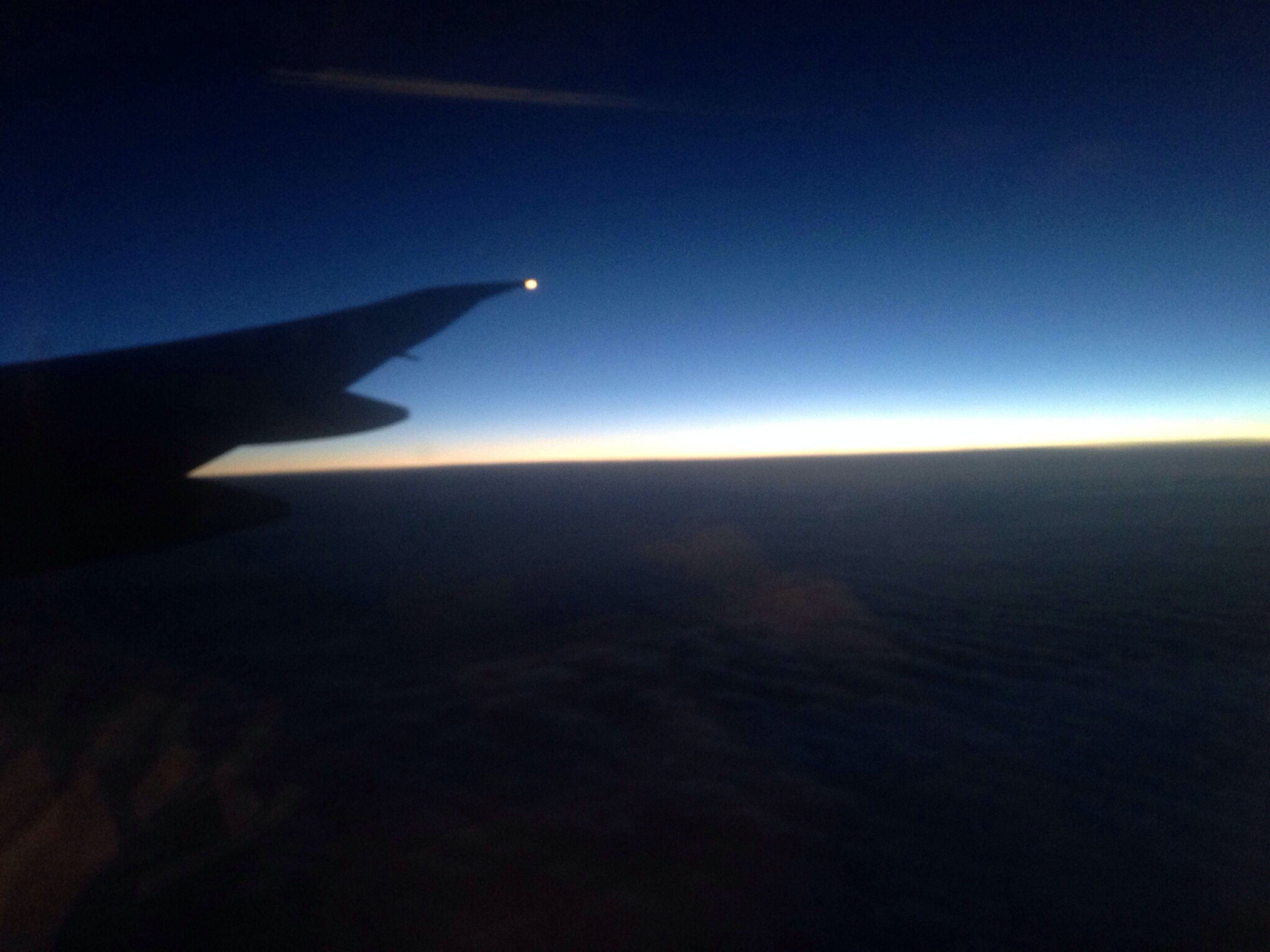 airplane, air vehicle, aircraft wing, flying, transportation, aerial view, part of, mode of transport, cropped, scenics, sky, mid-air, beauty in nature, travel, blue, journey, airplane wing, nature, sunset, tranquil scene