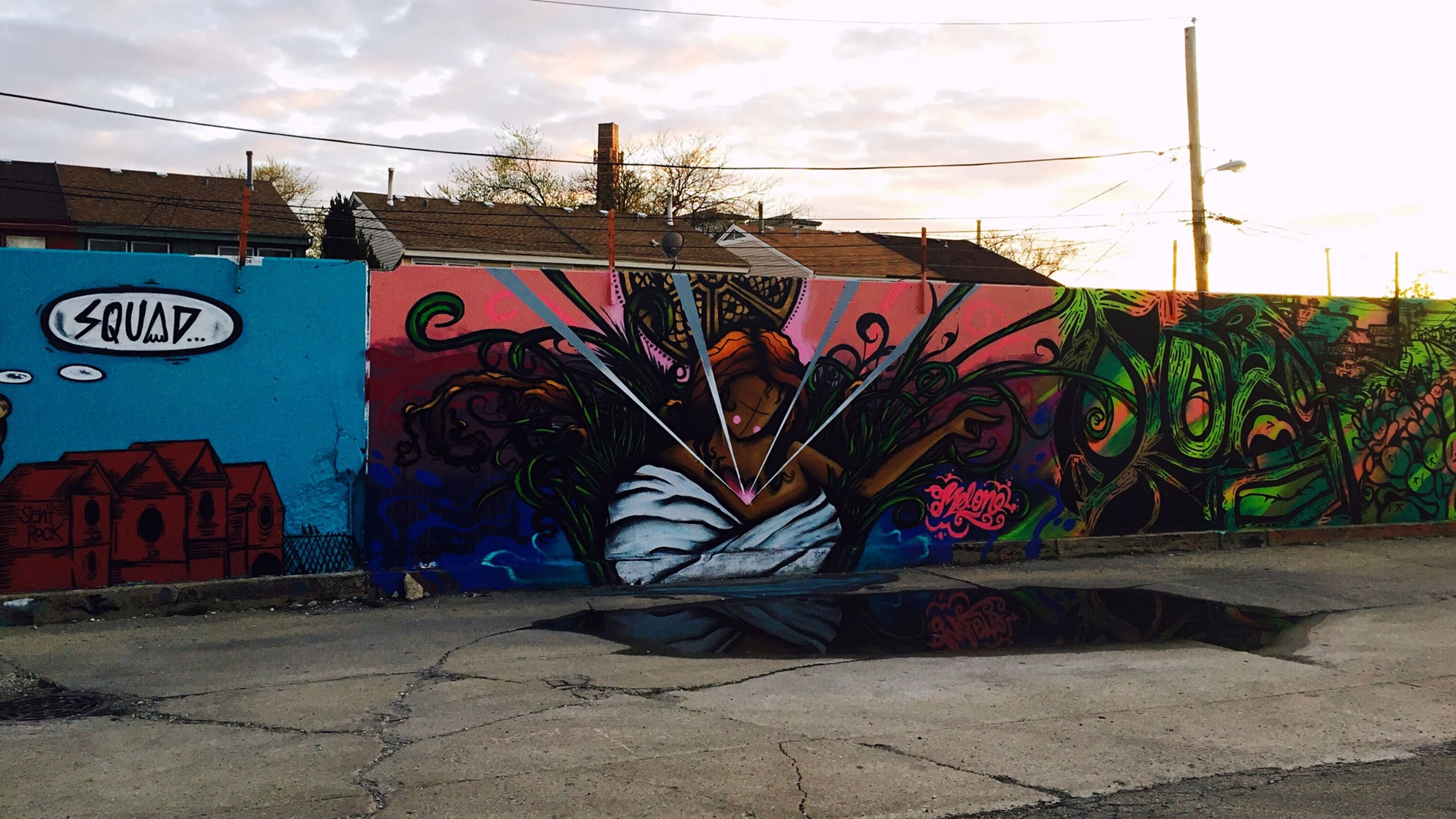 graffiti, architecture, built structure, building exterior, art, sky, wall - building feature, creativity, art and craft, text, street art, vandalism, day, transportation, outdoors, human representation, communication, western script, wall, power line