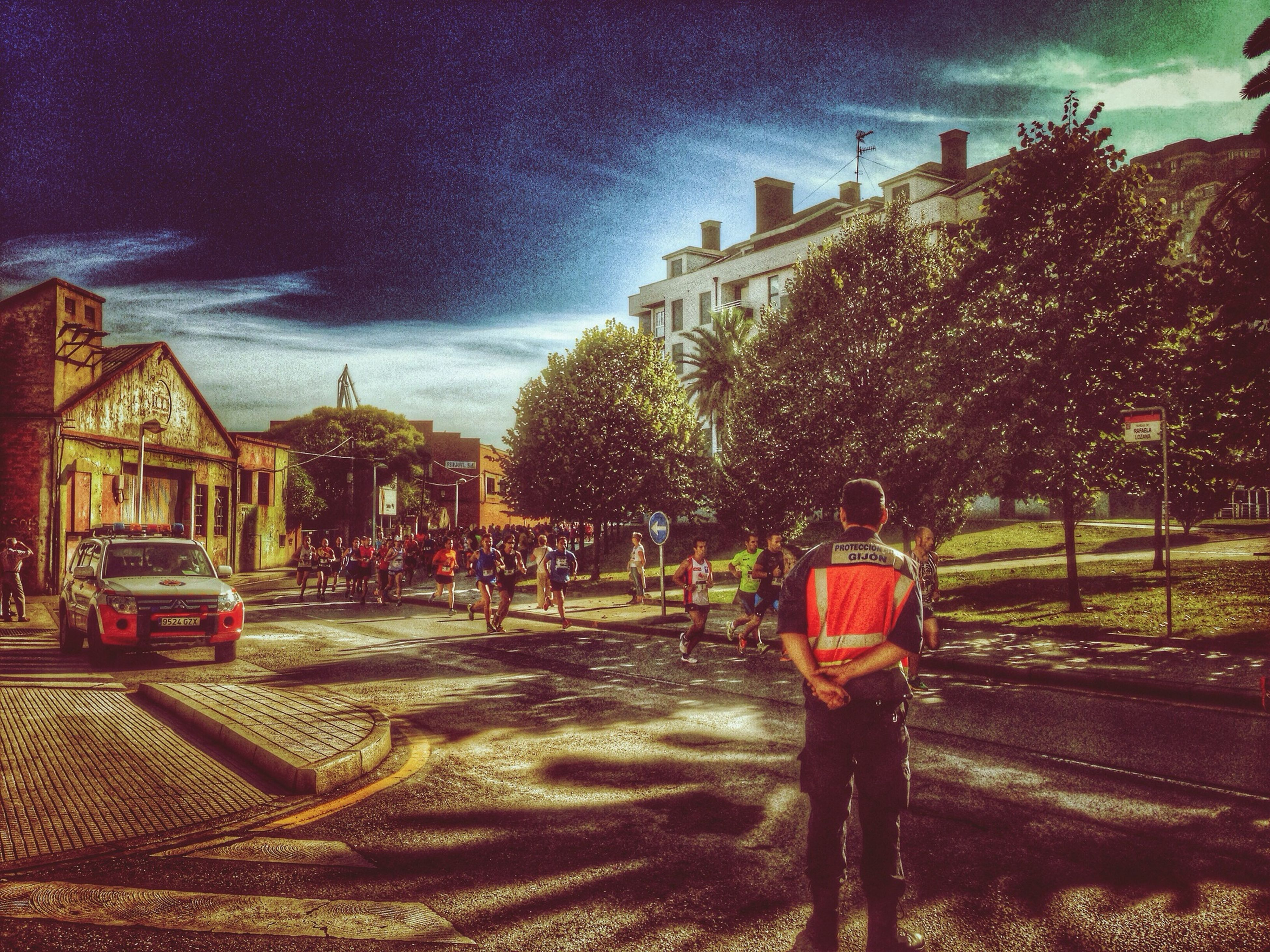 building exterior, sky, architecture, built structure, street, tree, city, cloud - sky, incidental people, city life, large group of people, car, person, outdoors, road, lifestyles, sunlight, house, residential structure