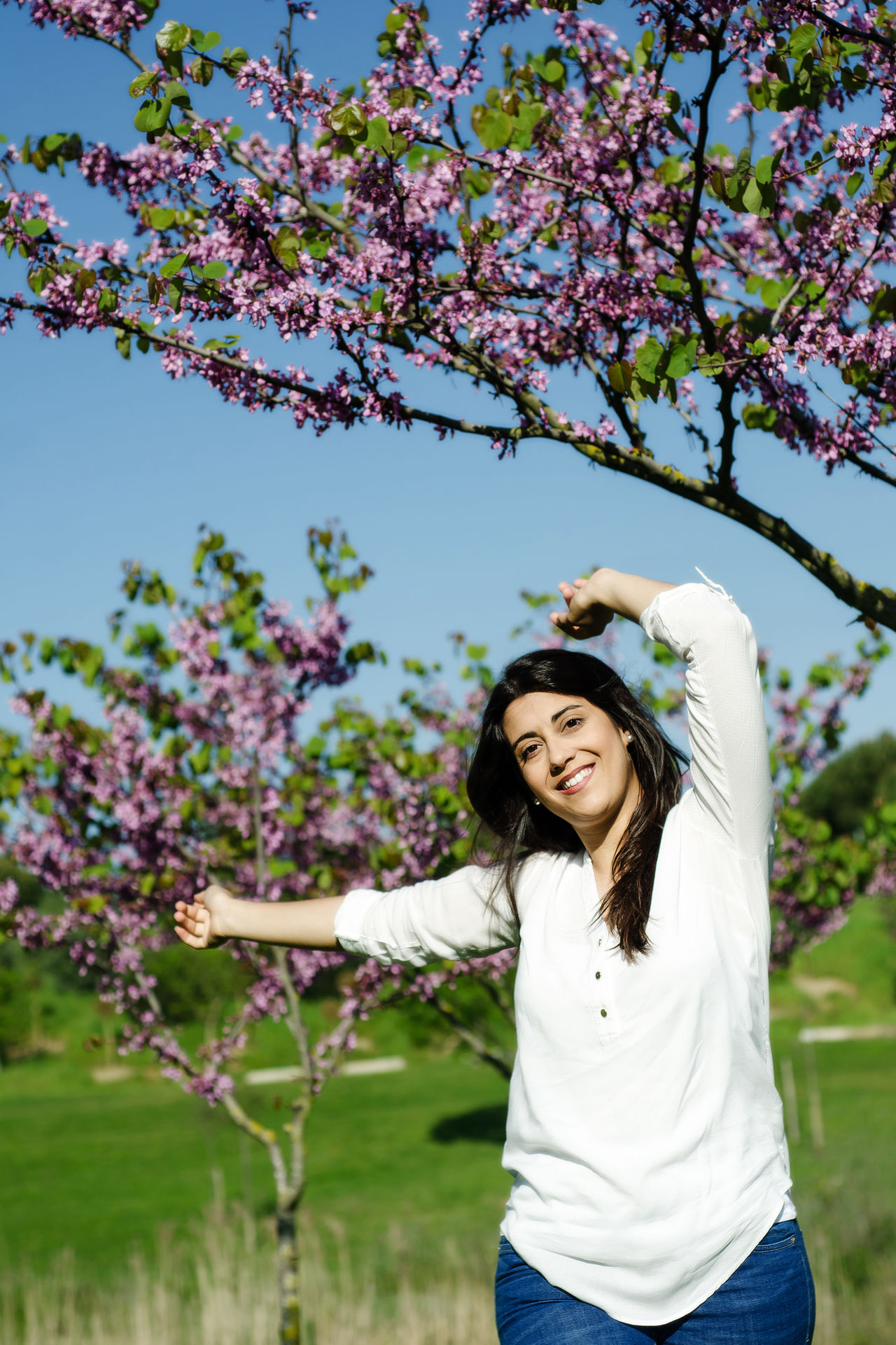Woman happy with live, enjoy´s the spring the city park Arms Raised Beautiful Woman Beauty In Nature Branch Casual Clothing Cheerful Day Flower Fragility Freshness Front View Growth Happiness Leisure Activity Long Hair Nature One Person Outdoors Real People Smiling Springtime Standing Tree Young Adult Young Women