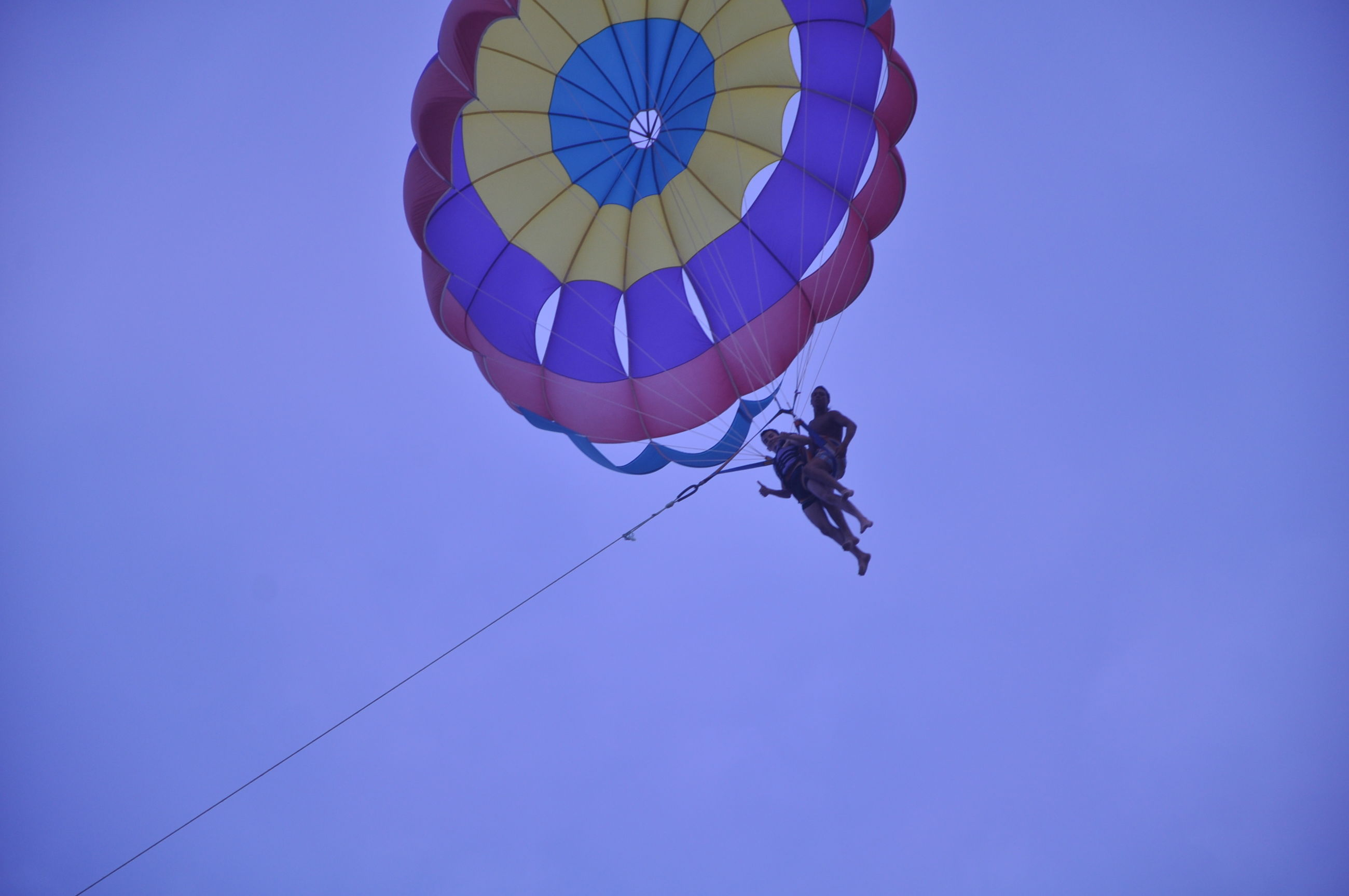 blue, low angle view, clear sky, flying, mid-air, copy space, transportation, air vehicle, multi colored, mode of transport, fun, sky, adventure, parachute, day, outdoors, kite - toy, no people, travel, freedom