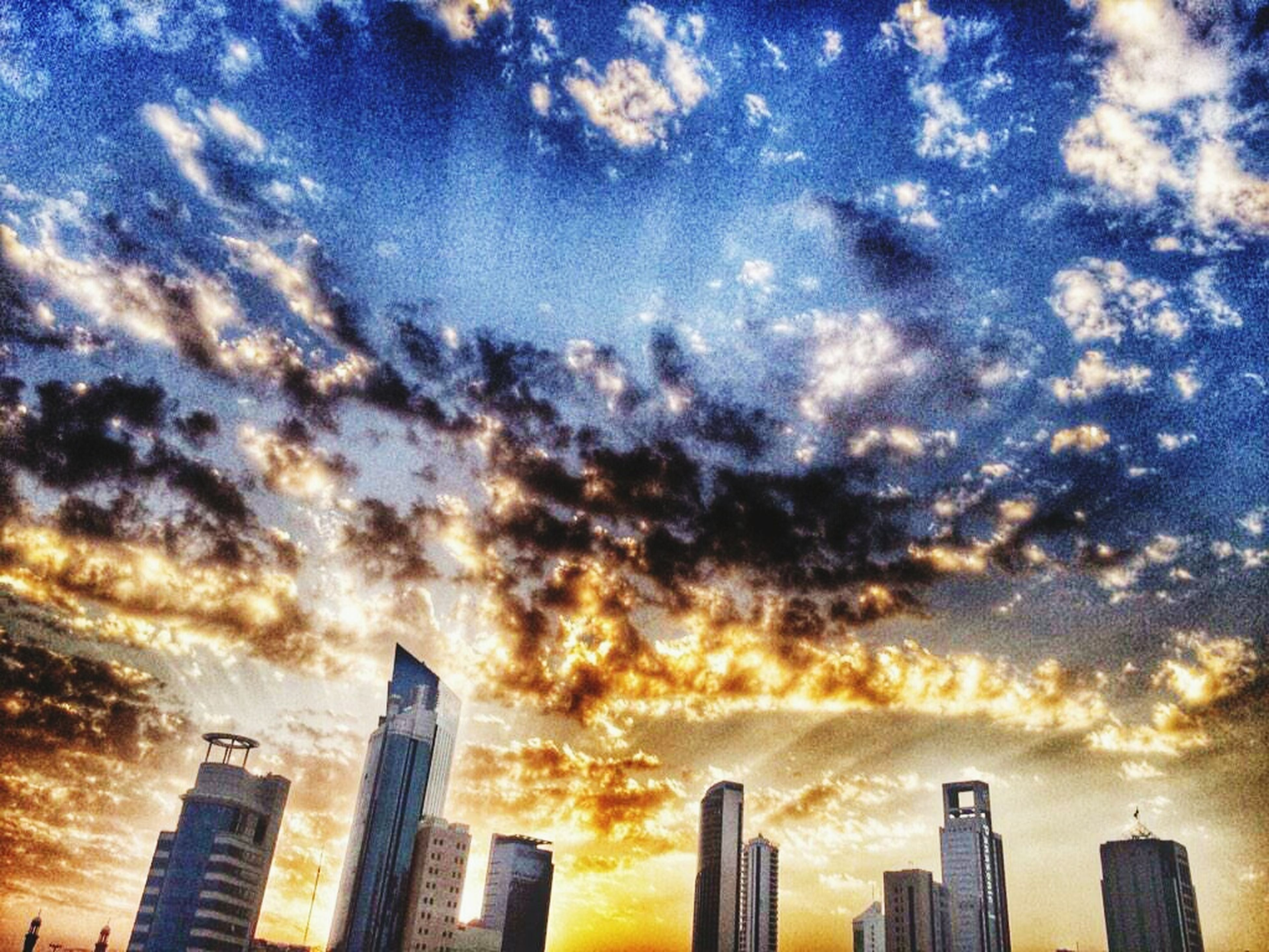 sky, building exterior, architecture, cloud - sky, built structure, city, skyscraper, cloudy, tall - high, cityscape, sunset, cloud, modern, urban skyline, weather, office building, low angle view, outdoors, tower, no people