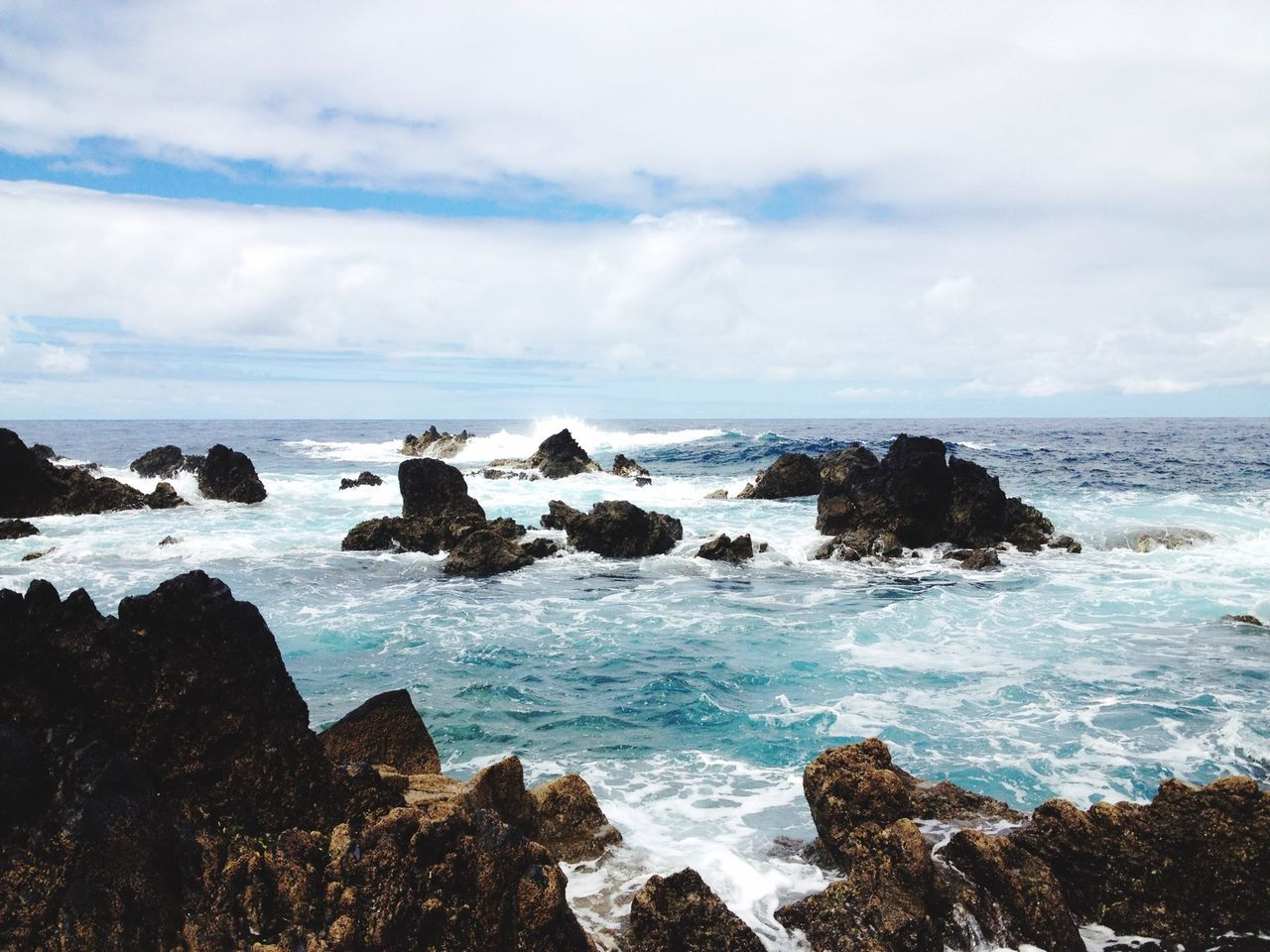 Scenic View Of Rocky Shore And Sea Against Cloudy Sky