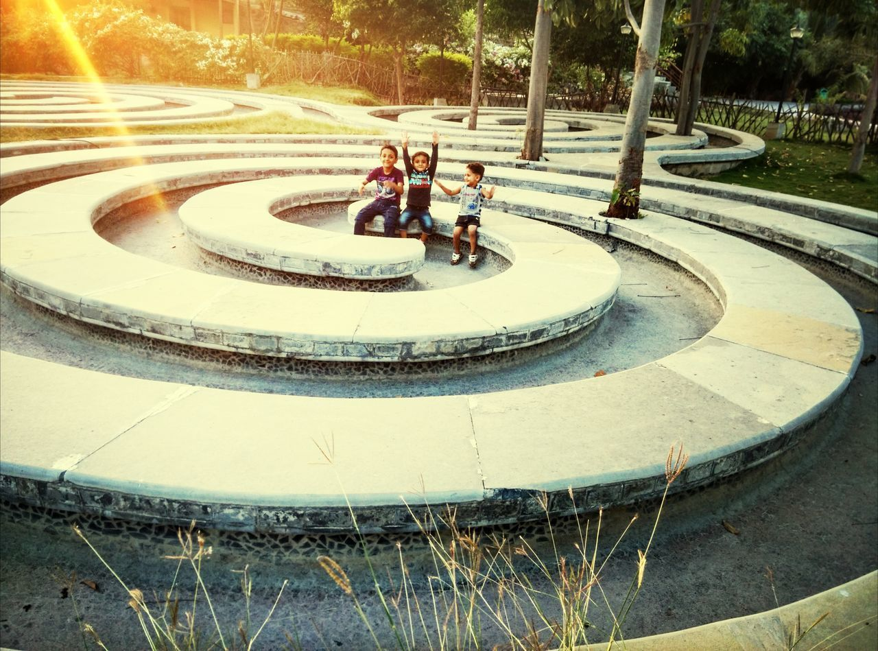 lifestyles, leisure activity, men, large group of people, person, high angle view, sunlight, shadow, park - man made space, tree, street, city life, city, walking, incidental people, travel, fountain, motion, bicycle