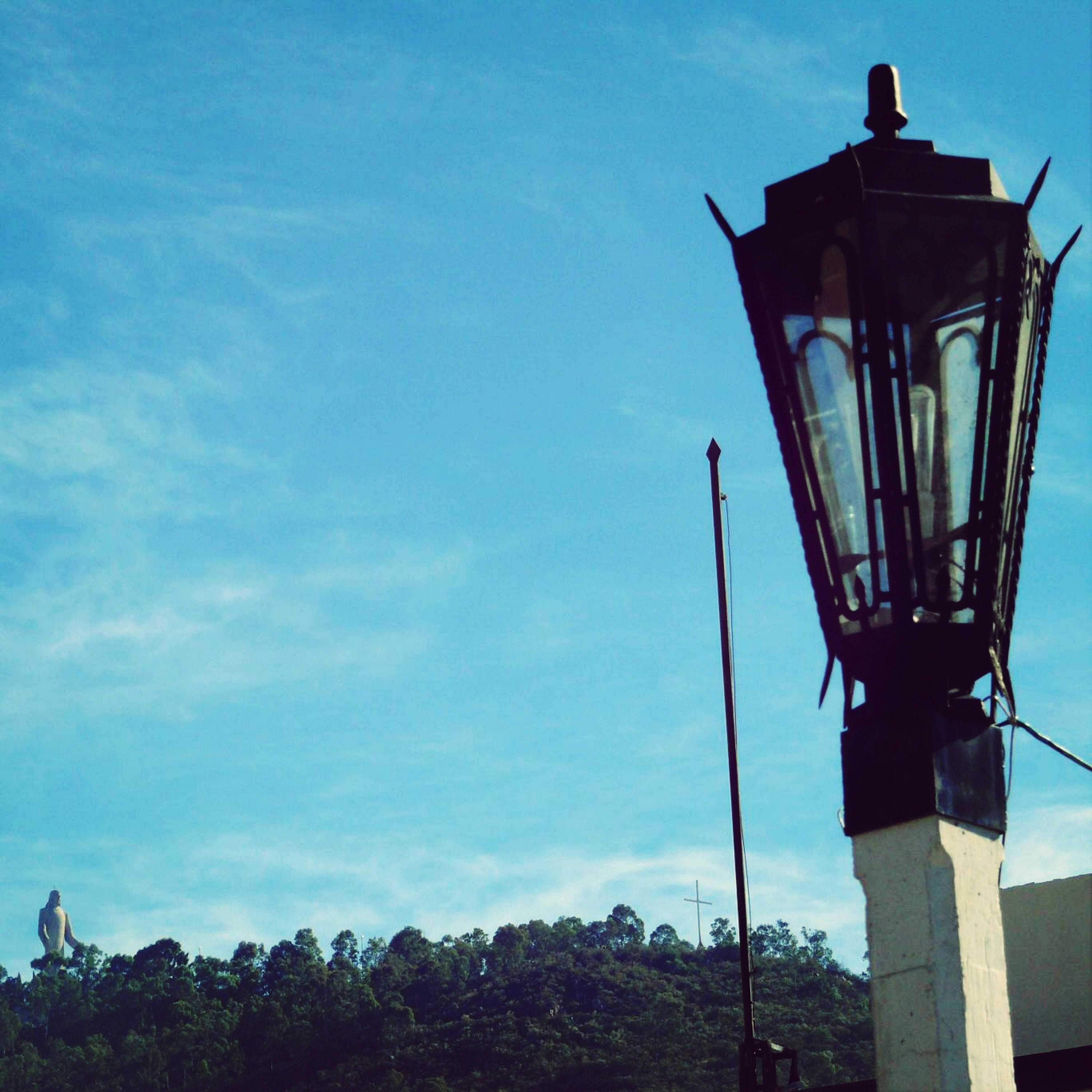 low angle view, sky, blue, street light, lighting equipment, pole, nature, tree, built structure, day, no people, cloud, outdoors, tranquility, cloud - sky, sunlight, clear sky, safety, protection, metal