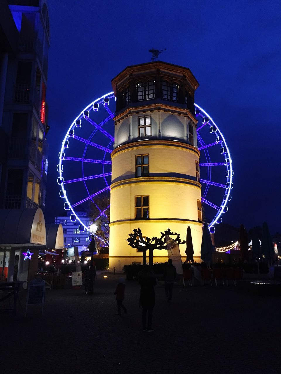 night, arts culture and entertainment, amusement park, illuminated, leisure activity, ferris wheel, built structure, architecture, amusement park ride, building exterior, real people, large group of people, outdoors, sky, enjoyment, blue, big wheel, women, men, people