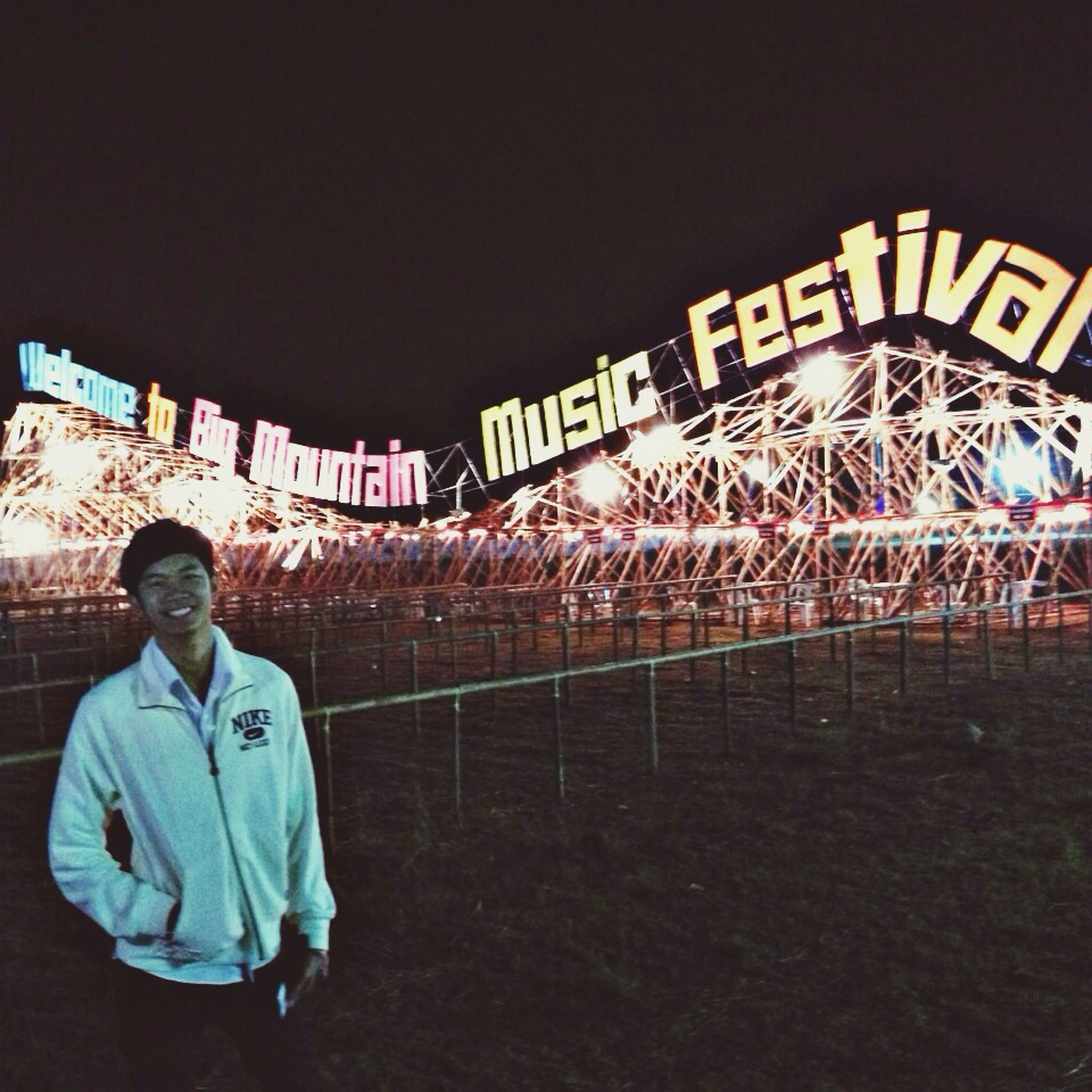 text, lifestyles, communication, western script, leisure activity, illuminated, men, casual clothing, night, standing, built structure, architecture, clear sky, non-western script, young men, sign, full length, three quarter length