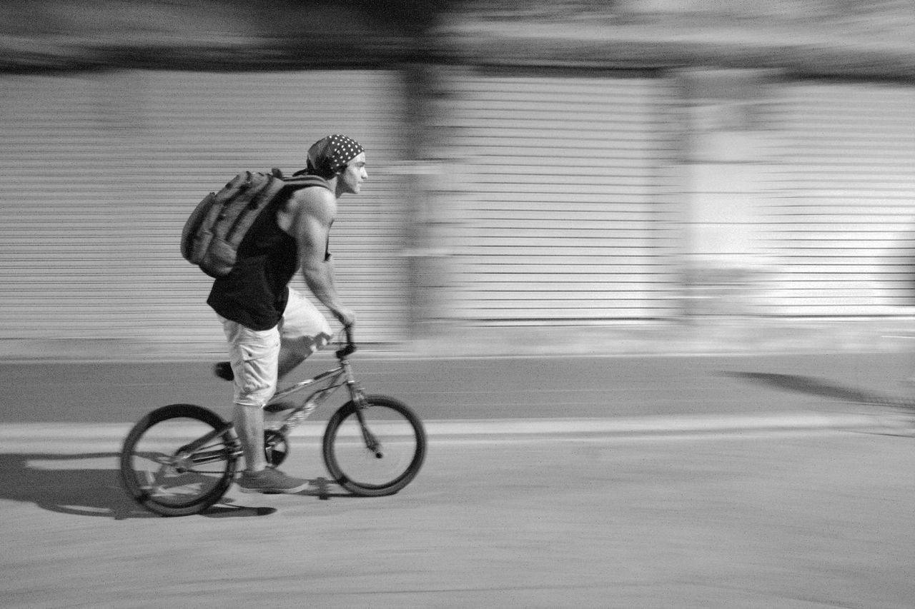 blurred motion, motion, full length, bicycle, speed, transportation, cycling, one person, riding, mode of transport, healthy lifestyle, road, exercising, men, day, real people, helmet, outdoors, city, headwear, young adult, one man only, adult, people, only men, adults only