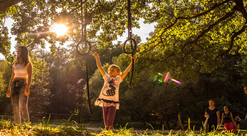 Adult Adventure Arms Raised Carefree Child Day Freedom Full Length Fun Fun Human Body Part Motion Nature Outdoors People Playing Rings Sport Sunset Togetherness Tree Vacations