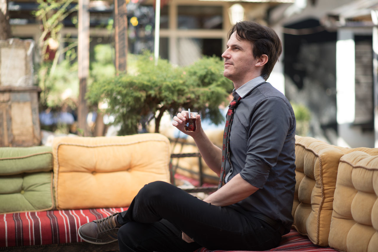 young man sitting and enjoying a cup of tea Adult Adults Only Business Business Person Businessman Day Full Length Indoors  Lifestyles Men One Man Only One Person Only Men People Plant Sitting Suit Think Well-dressed Zen Garden