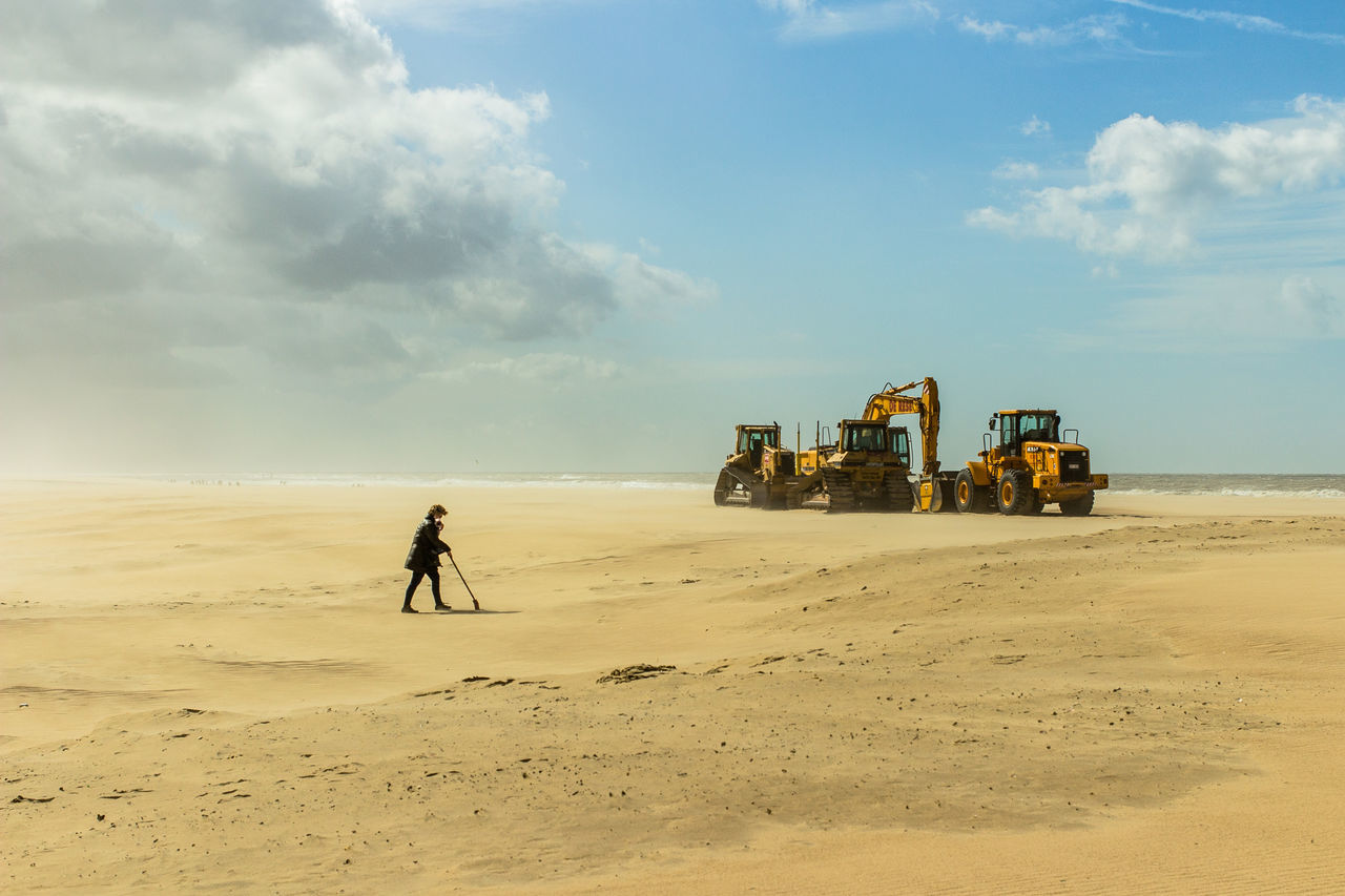 Woman Walking Against Earth Movers At Beach Against Sky