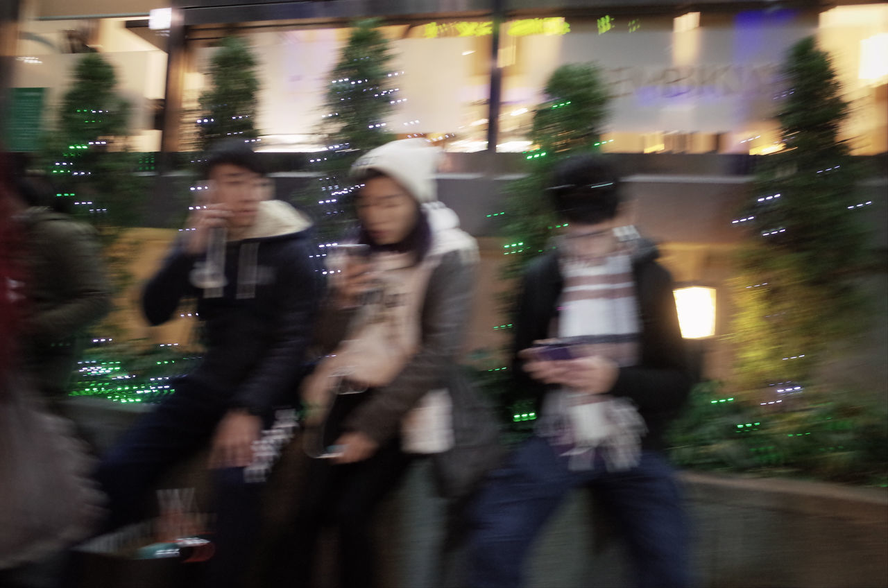 blurred motion, men, night, motion, real people, group of people, speed, leisure activity, togetherness, lifestyles, outdoors, illuminated, photographing, photography themes, women, city, friendship, defocused, technology, adult, people