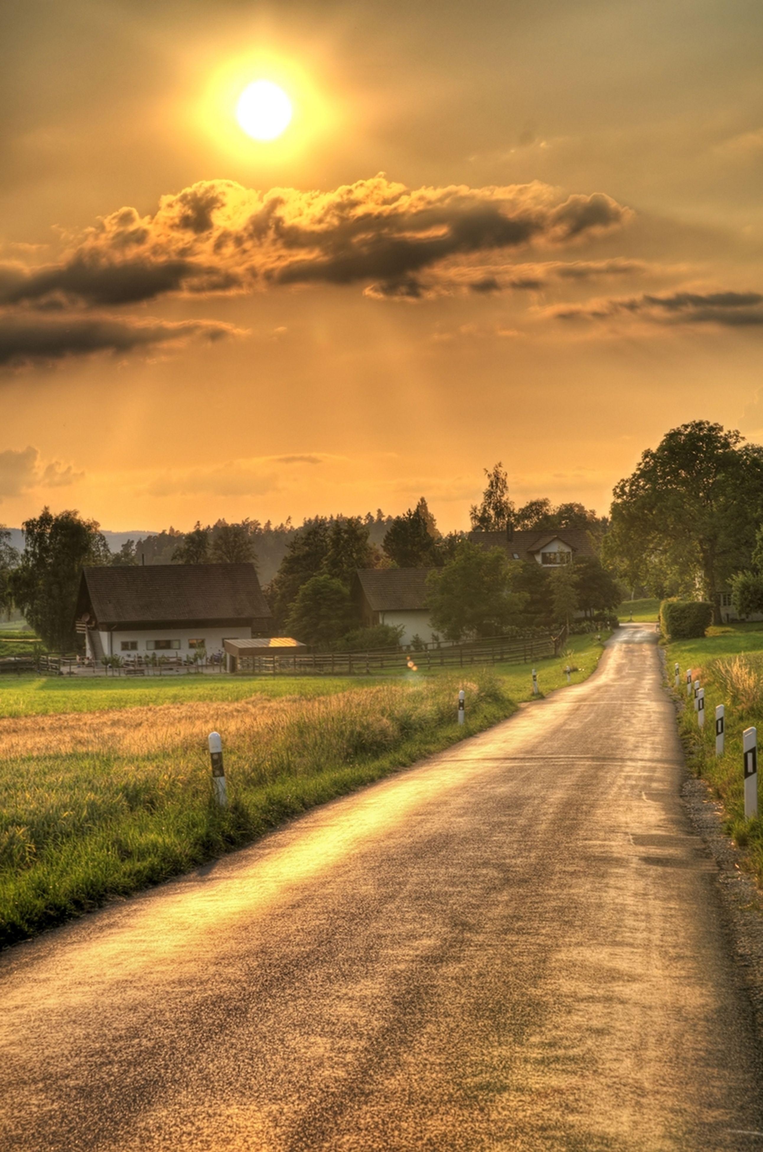 sunset, sky, the way forward, grass, field, sun, tree, landscape, cloud - sky, tranquility, tranquil scene, diminishing perspective, road, sunlight, nature, rural scene, vanishing point, scenics, beauty in nature, sunbeam