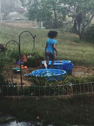 Casual Clothing Childhood Girls Grass Kiddie Pool Leisure Activity Lifestyles People Playing Playing In The Rain Rain Storm Rainy Day Play Real People Skipping The Great Outdoors - 2017 EyeEm Awards Water