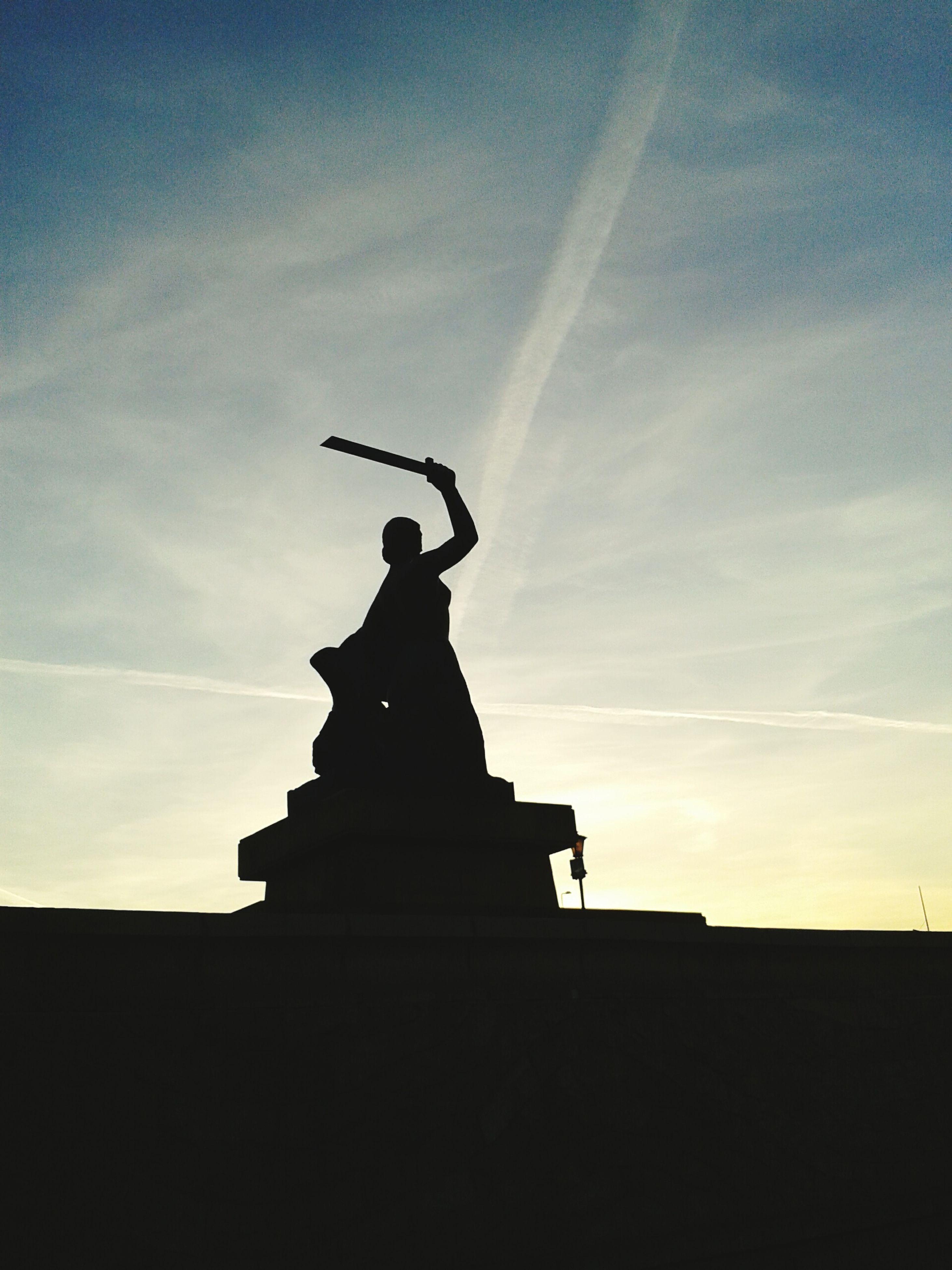 statue, silhouette, low angle view, sculpture, human representation, sky, art and craft, art, built structure, building exterior, architecture, creativity, cloud - sky, religion, cloud, sunset, dusk