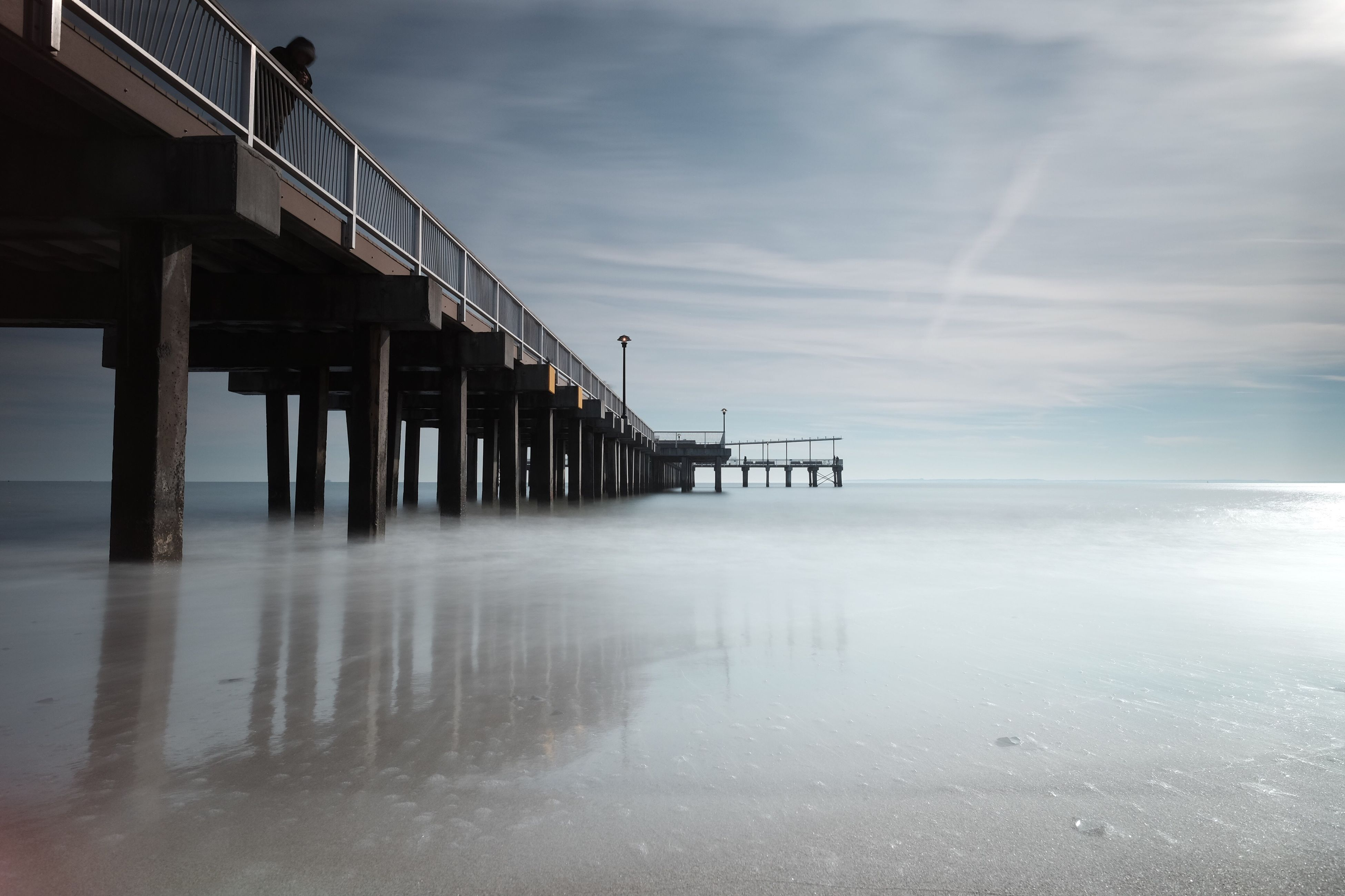 sea, water, beach, sky, horizon over water, pier, built structure, tranquility, tranquil scene, shore, reflection, sand, architecture, scenics, nature, beauty in nature, cloud - sky, waterfront, sunset, wave