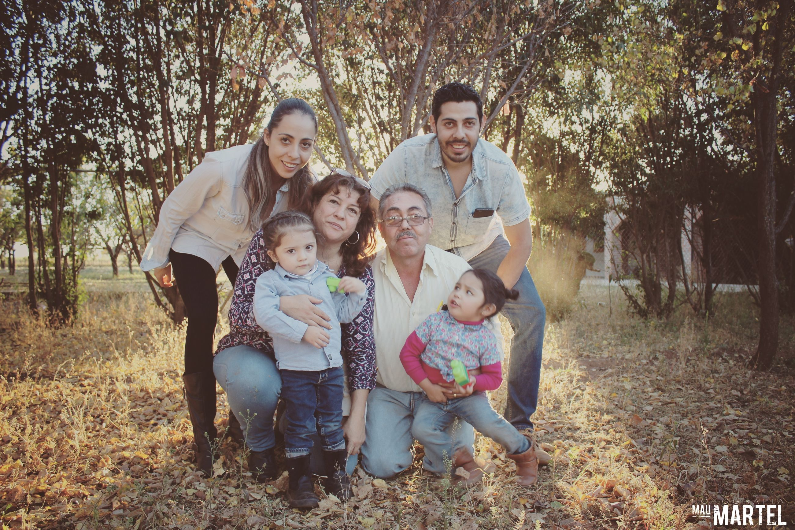 father, togetherness, tree, mother, mid adult, mid adult men, girls, boys, looking at camera, portrait, child, happiness, casual clothing, full length, daughter, family, son, front view, grass, day, childhood, outdoors, smiling, men, mature adult, women, sitting, females, bonding, lifestyles, forest, real people, nature, young women, young adult, adult, people