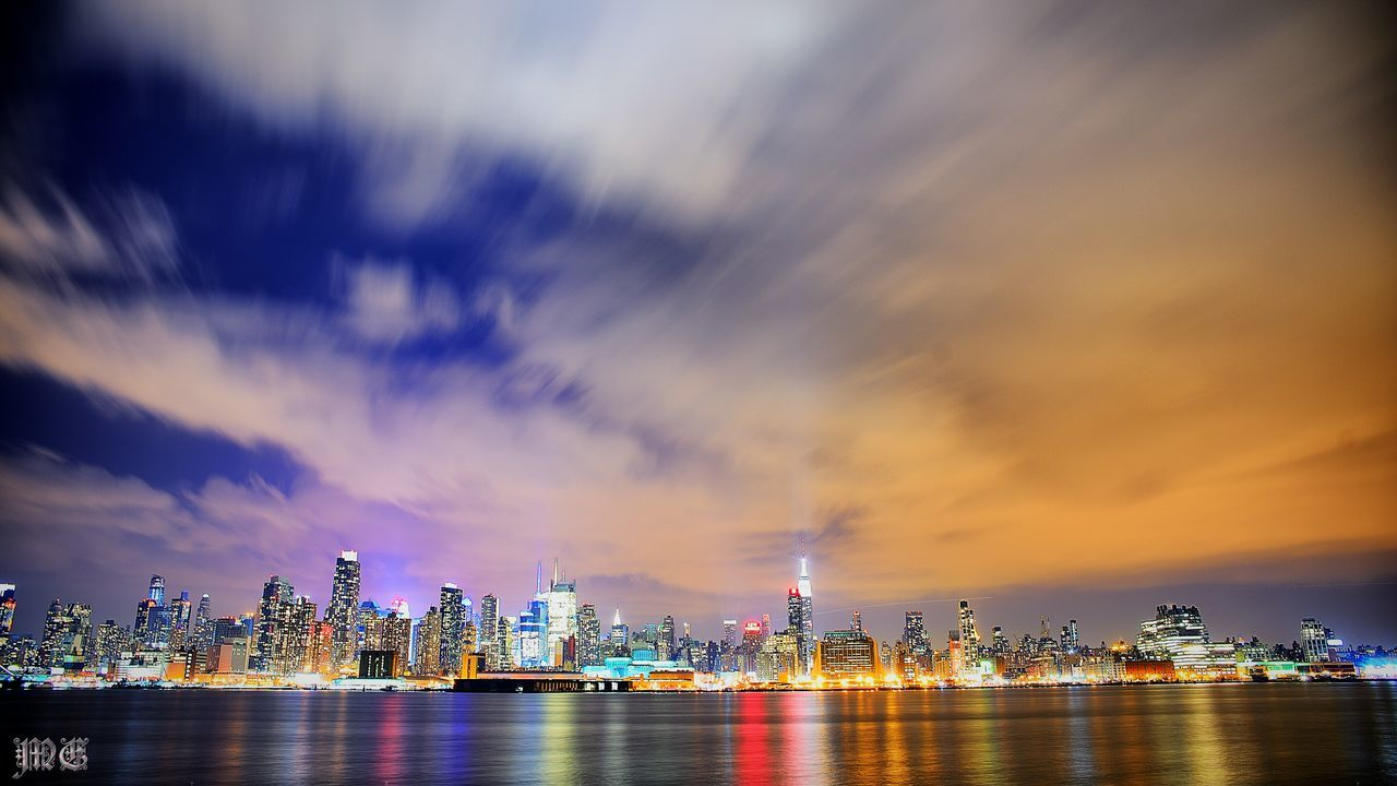 architecture, building exterior, skyscraper, cityscape, city, built structure, urban skyline, sky, sunset, illuminated, downtown district, modern, night, cloud - sky, travel destinations, river, financial district, waterfront, no people, water, outdoors, scenics, nature