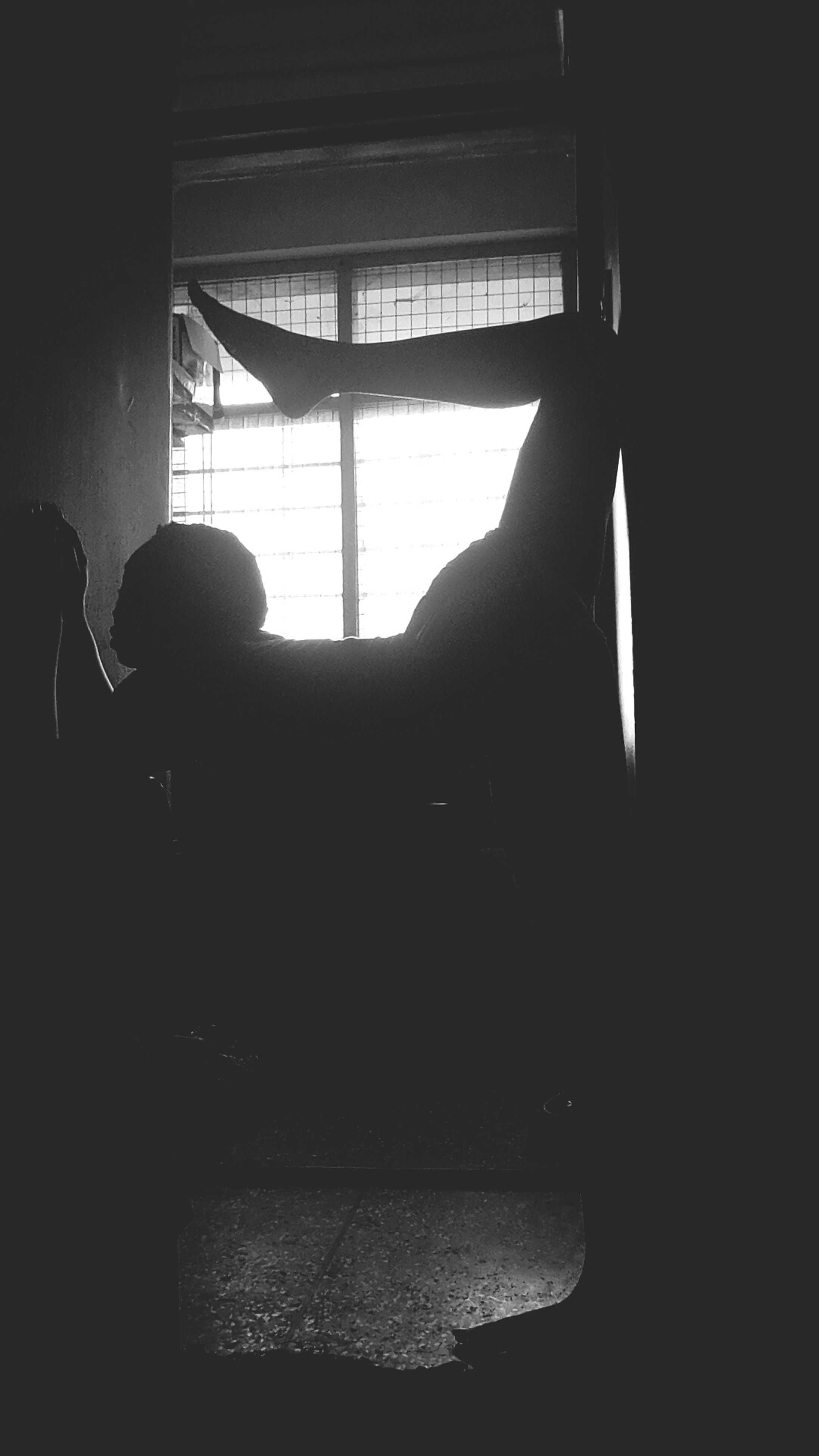 indoors, window, silhouette, lifestyles, sitting, dark, men, home interior, sunlight, person, looking through window, leisure activity, relaxation, glass - material, transparent, side view, standing, rear view