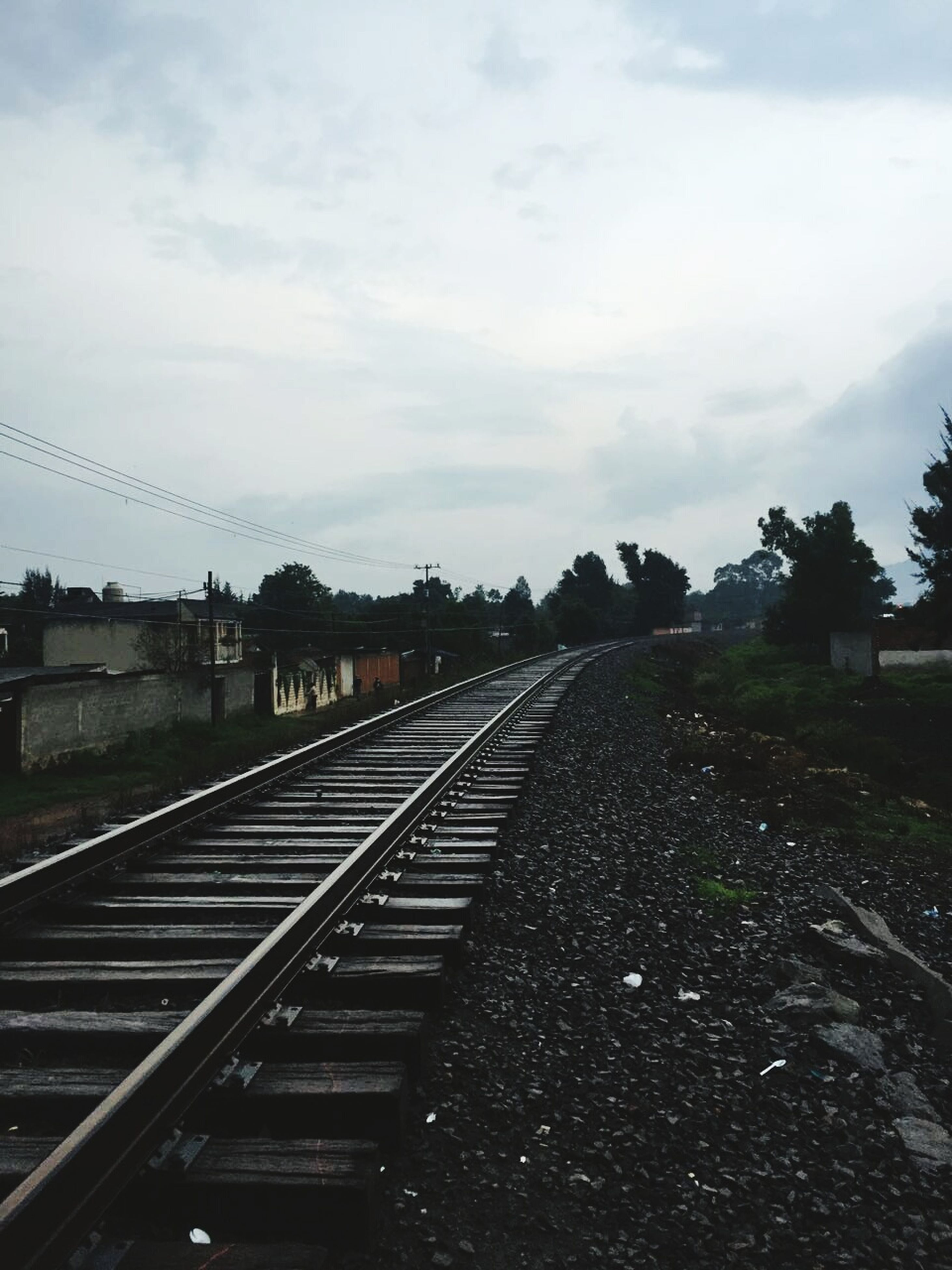railroad track, sky, rail transportation, transportation, cloud - sky, the way forward, tree, diminishing perspective, vanishing point, connection, railway track, built structure, cloudy, public transportation, cloud, growth, nature, outdoors, day, field