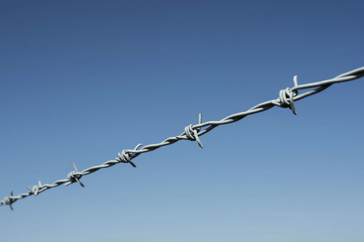 Single barbed wire on a fence against a bright clear blue sky. Barbed Wire Blue Sky Border Chainlink Fence Close-up Danger Day Exclusion EyeEmNewHere Fence Metal Metal Wire No People Outdoors Protection Razor Razor Wire Safety Security Security System Segregation  Sky Spiked Wall Wire