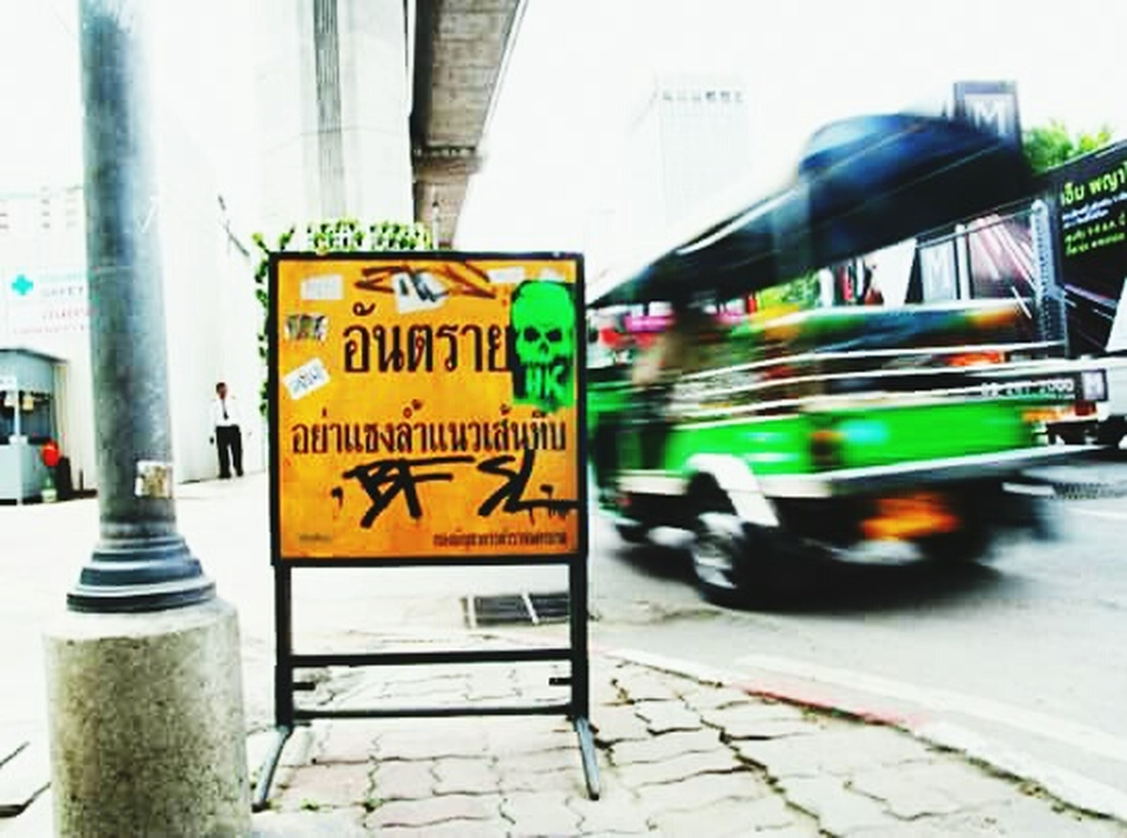 text, western script, built structure, architecture, communication, building exterior, city, transportation, street, information sign, city life, blurred motion, non-western script, incidental people, sign, road sign, road, motion, yellow, city street
