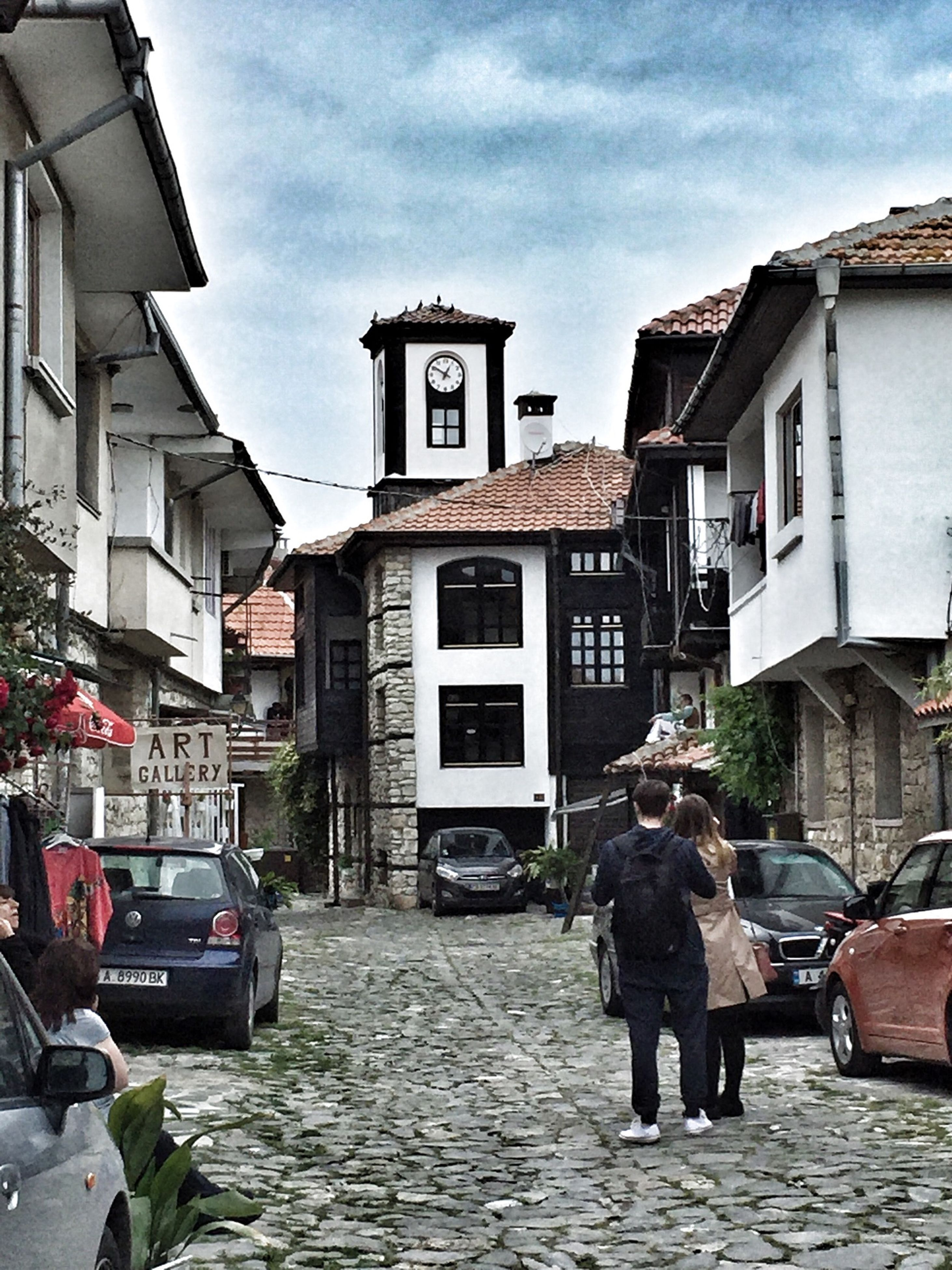 building exterior, architecture, built structure, men, lifestyles, street, sky, rear view, full length, walking, person, transportation, leisure activity, cobblestone, casual clothing, the way forward, mode of transport