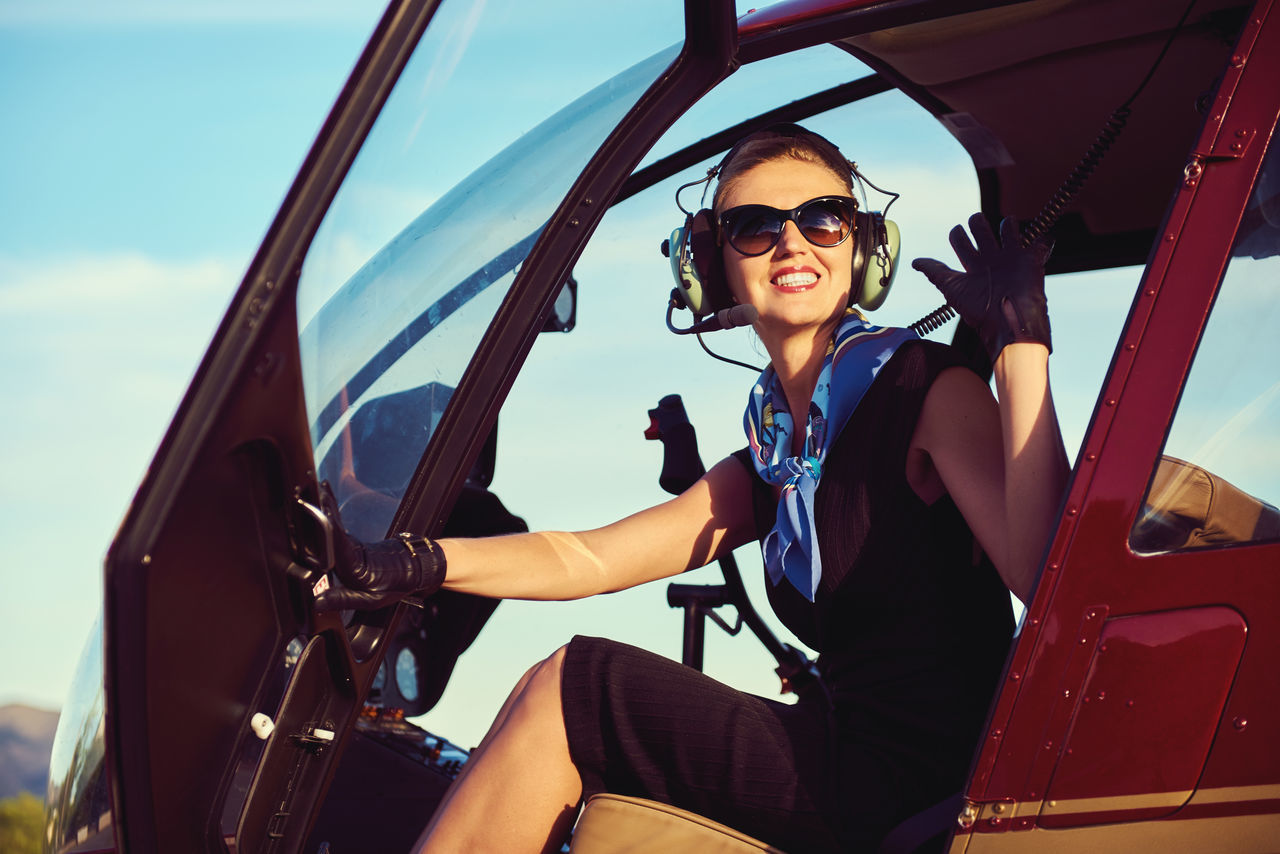 Attractive woman pilot sitting in the helicopter 30s Air Vehicle Aircraft Aircrew Aviator Beautiful Woman Business Woman Cabin Crew Caucasian Female Flight Headphones Helicopter Inside Landing Field Lifestyles Mode Of Transport One Person People Pilot Smiling Sunglasses Sunny Day Transportation Young Women