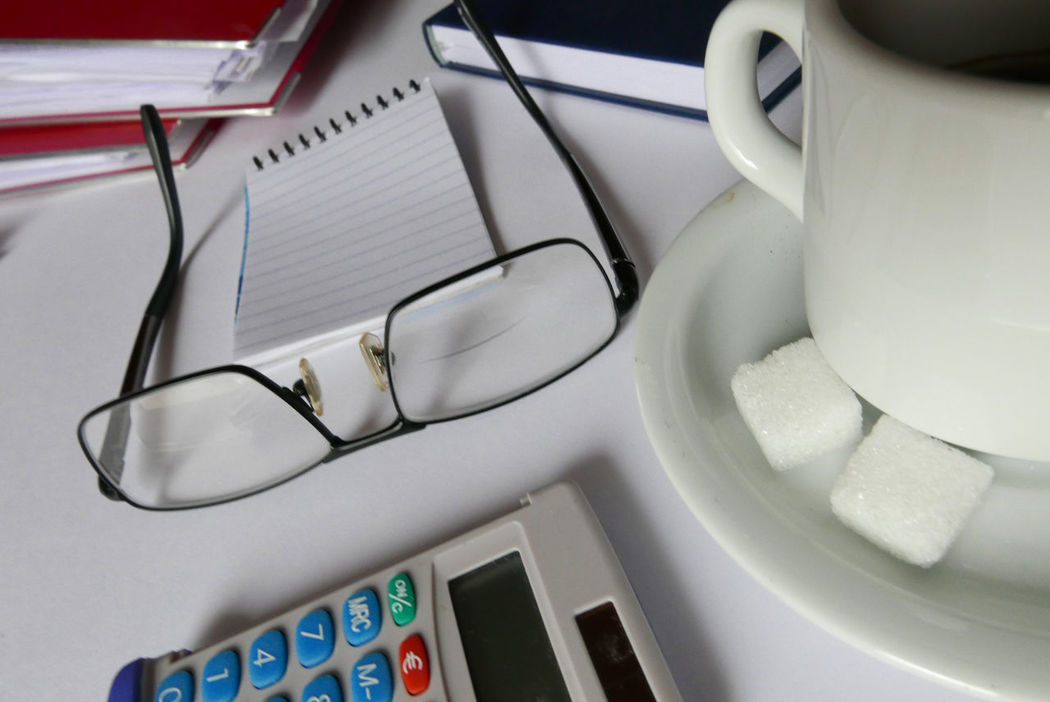 Close-up Cropped Detail Indoors  Still Life Technology Eyeglasses  Notebook Cup Of Coffee Sugar Calculator Working Home Working Business Desk
