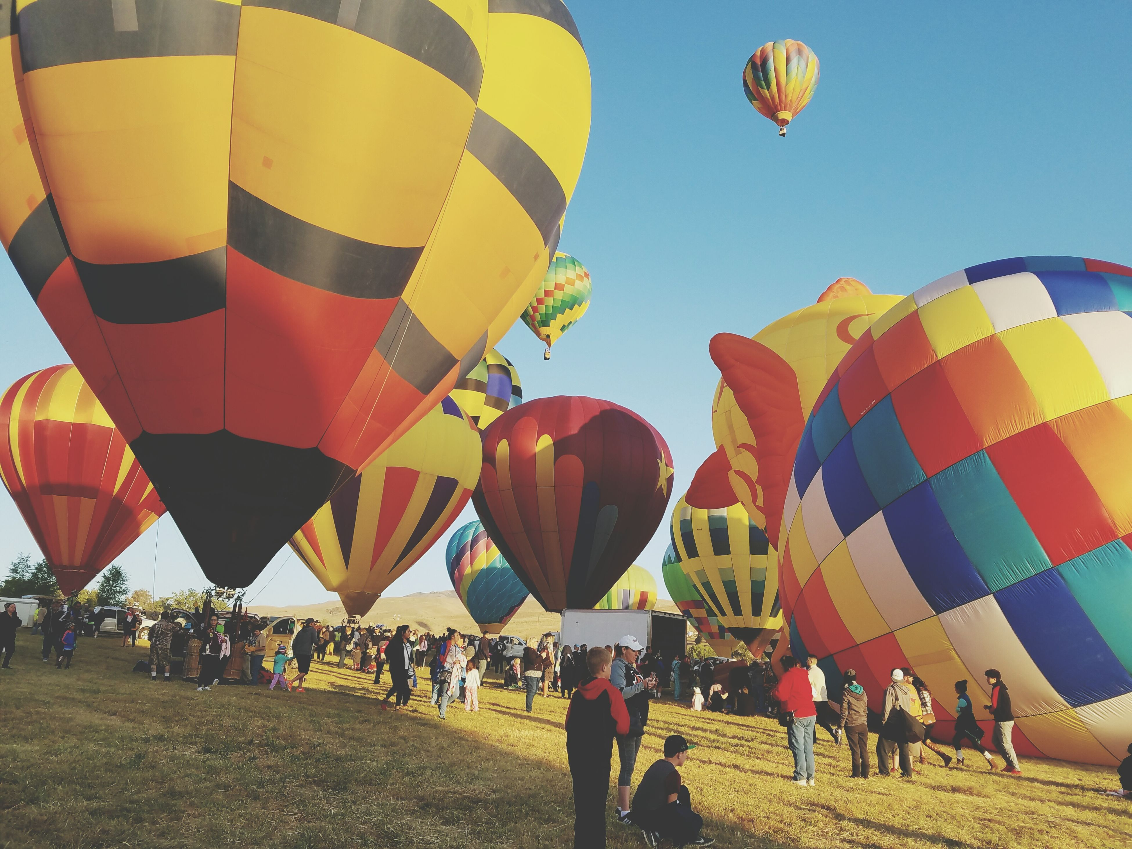 multi colored, large group of people, hot air balloon, clear sky, tourism, tourist, traditional festival, flying, leisure activity, person, mid-air, variation, travel destinations, travel, cultures, group of objects, hanging, lantern, day, paper lantern, city, sky, outdoors, sunny, decoration, lawn, event, enjoyment, fun, amusement park
