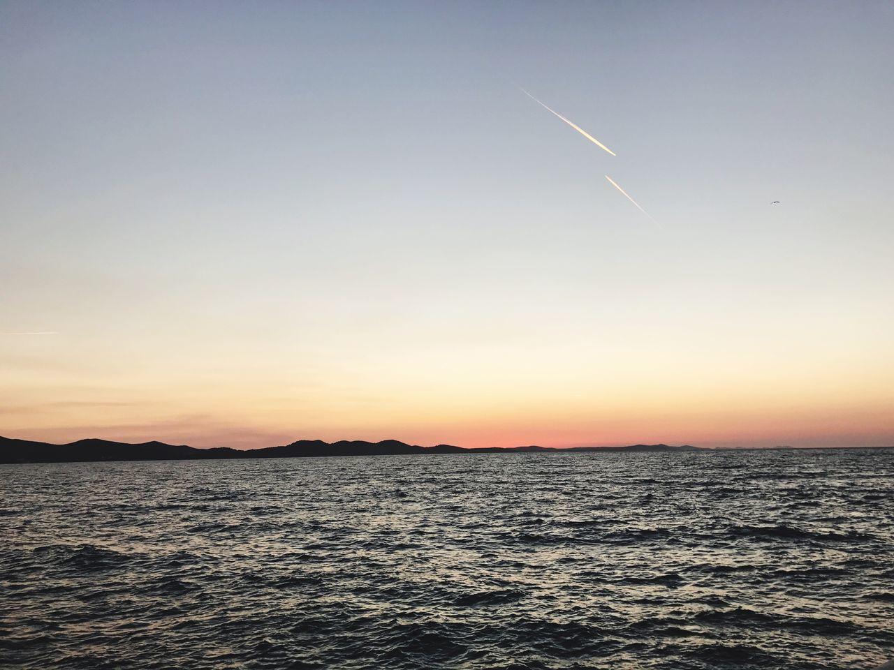 Sunset Beauty In Nature Scenics Nature Vapor Trail Sea Tranquil Scene Tranquility Sky No People Outdoors Waterfront Contrail Silhouette Water Clear Sky Horizon Over Water Day