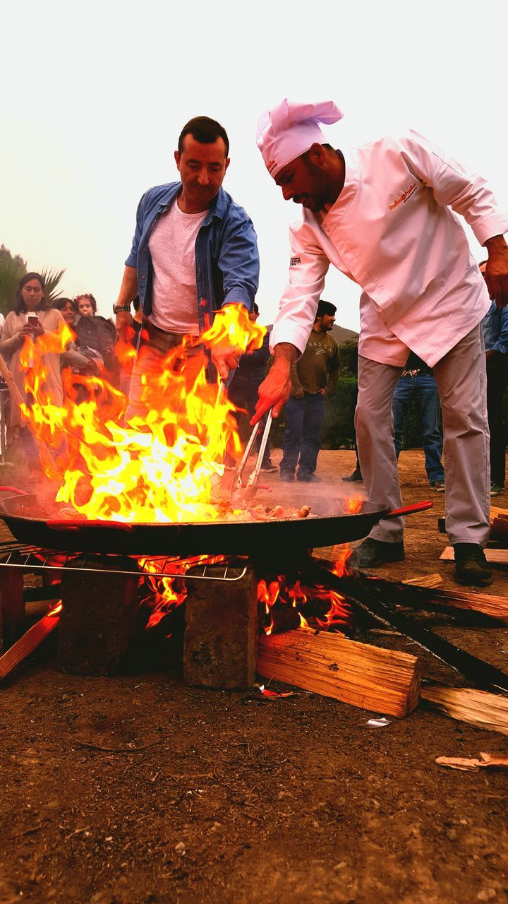 real people, two people, burning, flame, standing, casual clothing, full length, togetherness, front view, young men, young adult, men, heat - temperature, outdoors, occupation, day, working, food, sky, people