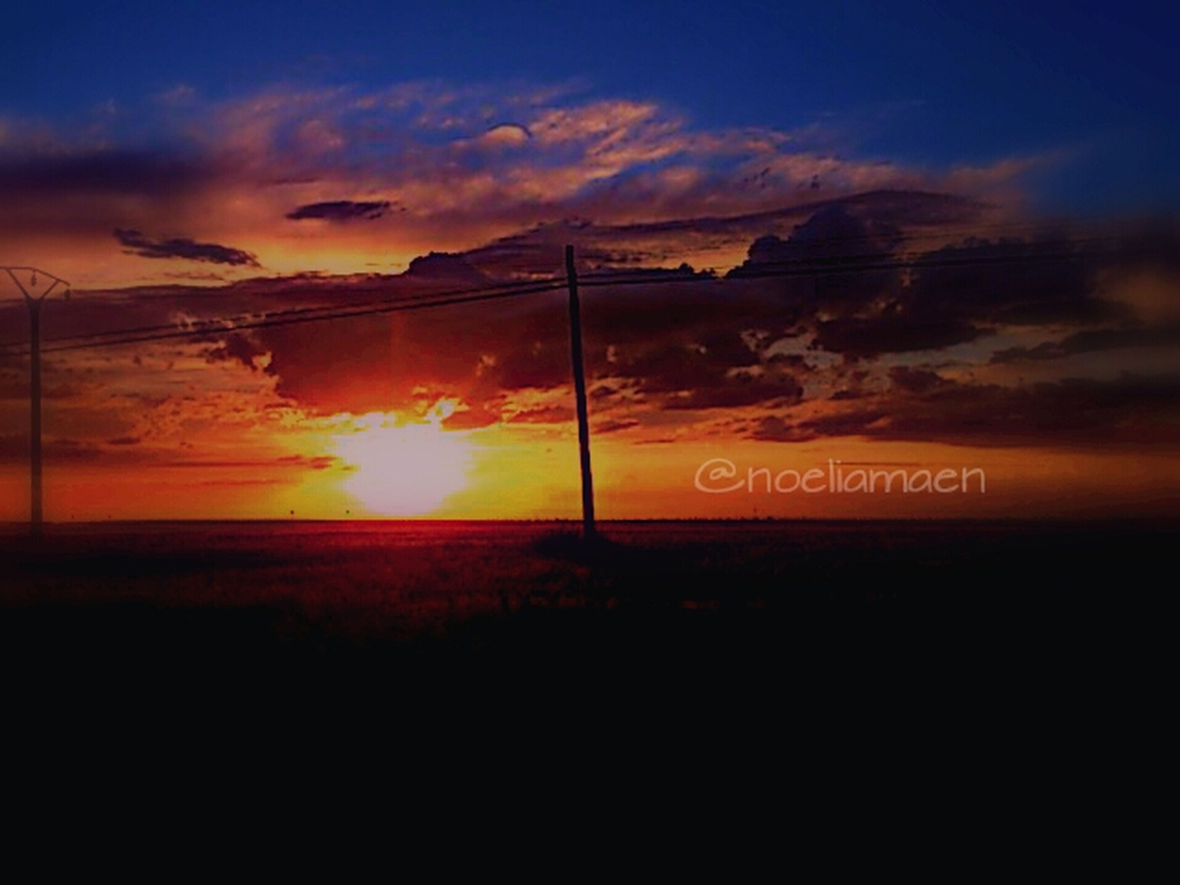 sunset, sky, cloud - sky, orange color, scenics, communication, text, silhouette, tranquility, tranquil scene, beauty in nature, landscape, western script, cloud, nature, idyllic, sun, cloudy, dramatic sky, outdoors