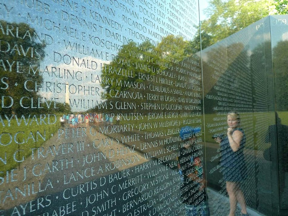 Reflection on Vietnam War Memorial in Washington DC Names of Soldiers Inscribed in Black Granite that died. Very Powerful Memorial. The Tourist
