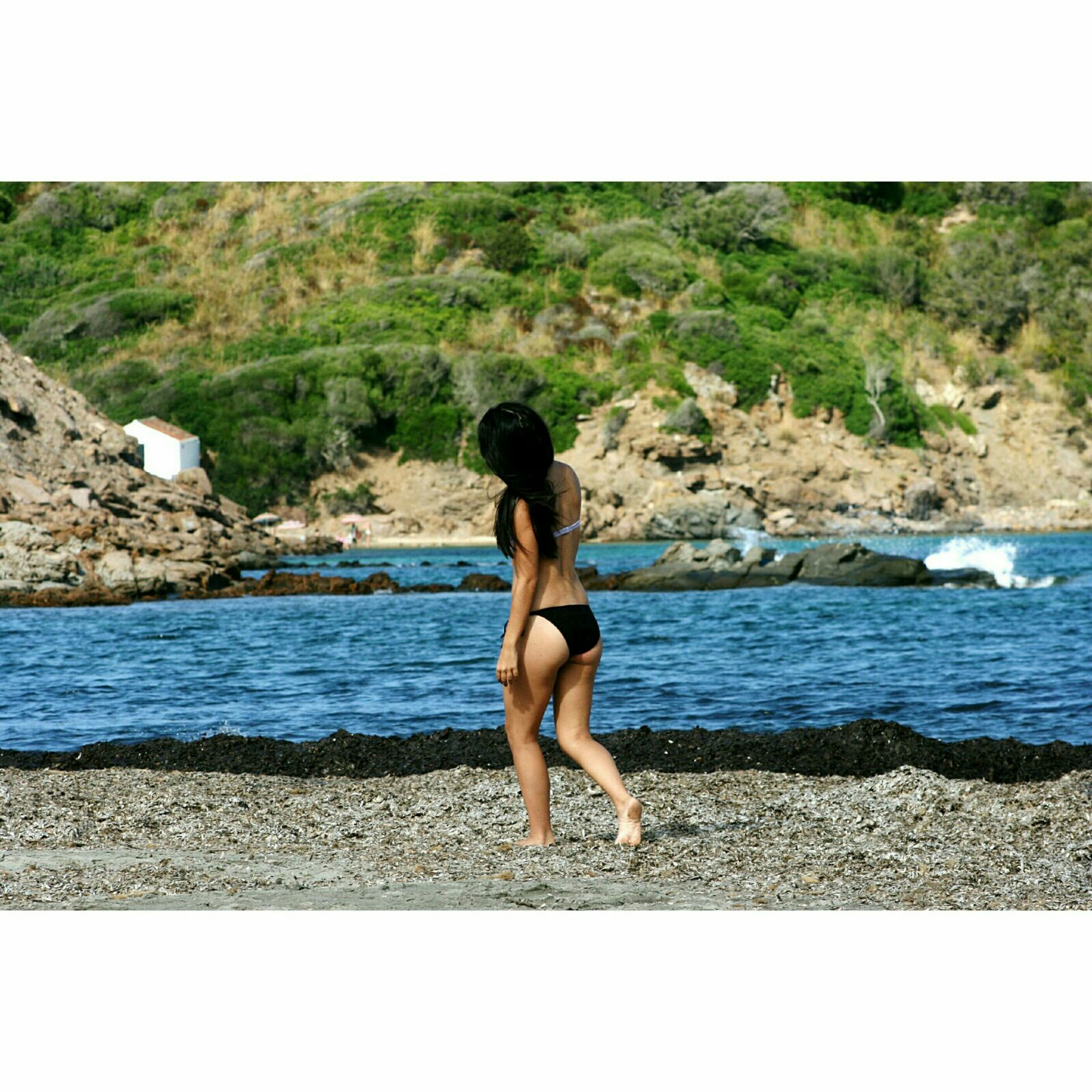 full length, water, lifestyles, transfer print, leisure activity, young adult, standing, auto post production filter, casual clothing, young women, tranquility, rear view, nature, sea, mountain, beauty in nature, person, tranquil scene