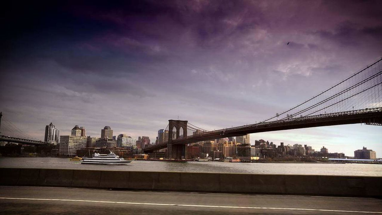 bridge - man made structure, architecture, built structure, connection, city, engineering, suspension bridge, transportation, river, sky, travel destinations, skyscraper, modern, cityscape, urban skyline, travel, cloud - sky, building exterior, downtown district, outdoors, waterfront, bridge, night, illuminated, water, no people