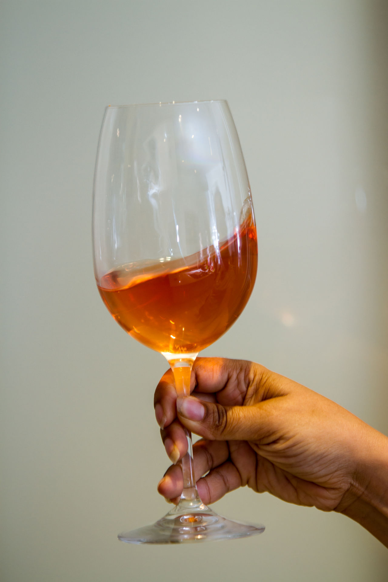 African American female swirling a wine glass half full of rose wine Adult Adults Only Alcohol Celebratory Toast Close-up Day Drink Drinking Drinking Glass Food And Drink Gray Background Half Full Holding Human Body Part Human Hand Indoors  One Person One Woman Only Only Women People Studio Shot Wine Wineglass Winetasting