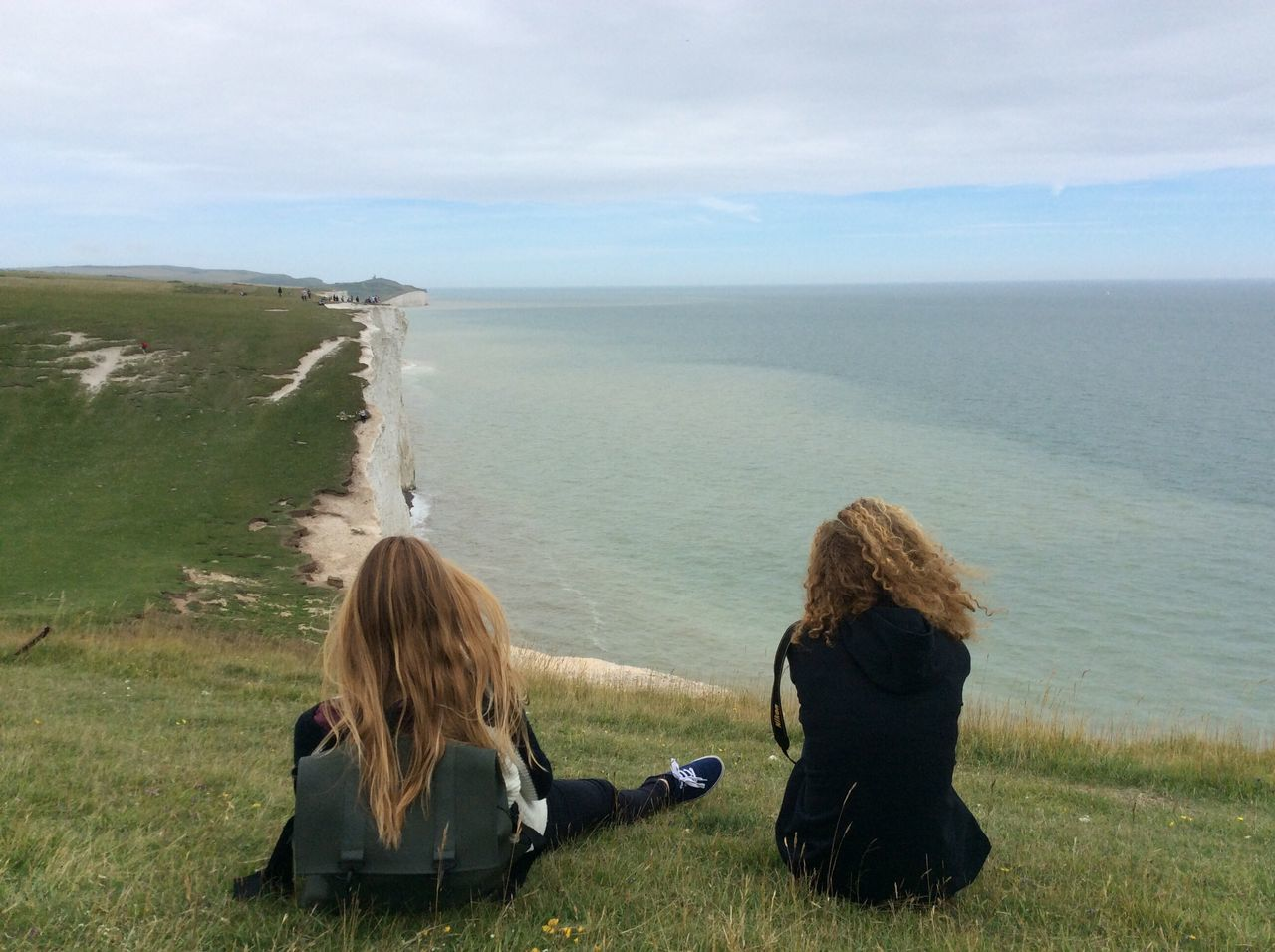 Rear View Of Women Sitting On Grass At Seven Sisters While Looking At Horizon