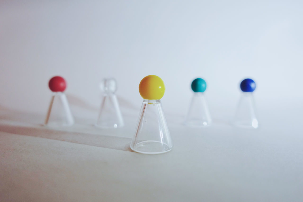 Group of colorful game pawns on white background Being Business Colorful Concept Conceptual Copy Space Counter Crowd Different Game Group Horizontal Individuality Leader Leadership Leading Manager Objects Pawn Standing Out Standing Out From The Crowd Team Team Leader Teamwork White Background
