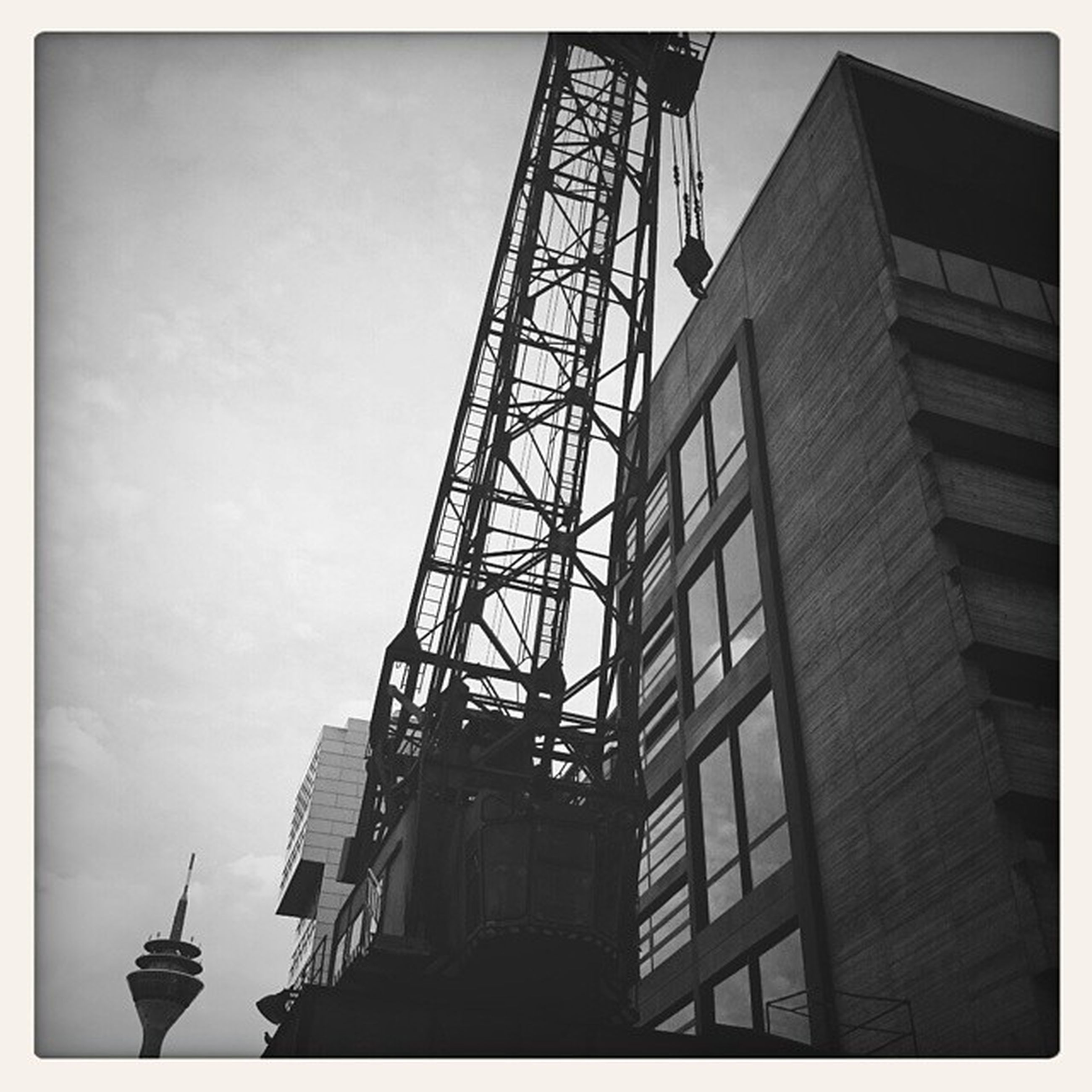 architecture, built structure, low angle view, transfer print, building exterior, auto post production filter, sky, tower, metal, tall - high, construction site, development, construction, day, no people, city, outdoors, tall, metallic, crane - construction machinery