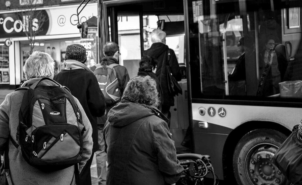 real people, rear view, transportation, land vehicle, men, mode of transport, street, large group of people, occupation, public transportation, day, car, women, bus, lifestyles, outdoors, road, city, building exterior, working, crowd, adult, people, adults only