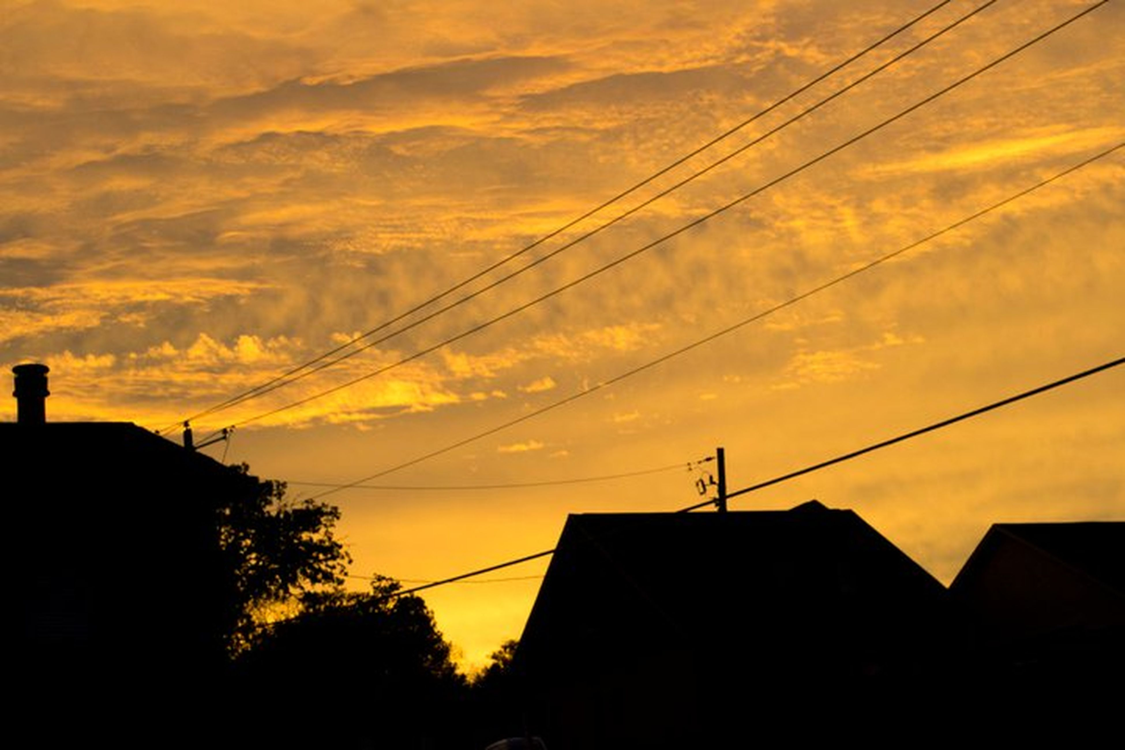 sunset, building exterior, architecture, silhouette, built structure, power line, sky, low angle view, house, orange color, cable, electricity pylon, residential structure, cloud - sky, residential building, cloud, electricity, power supply, tree, high section