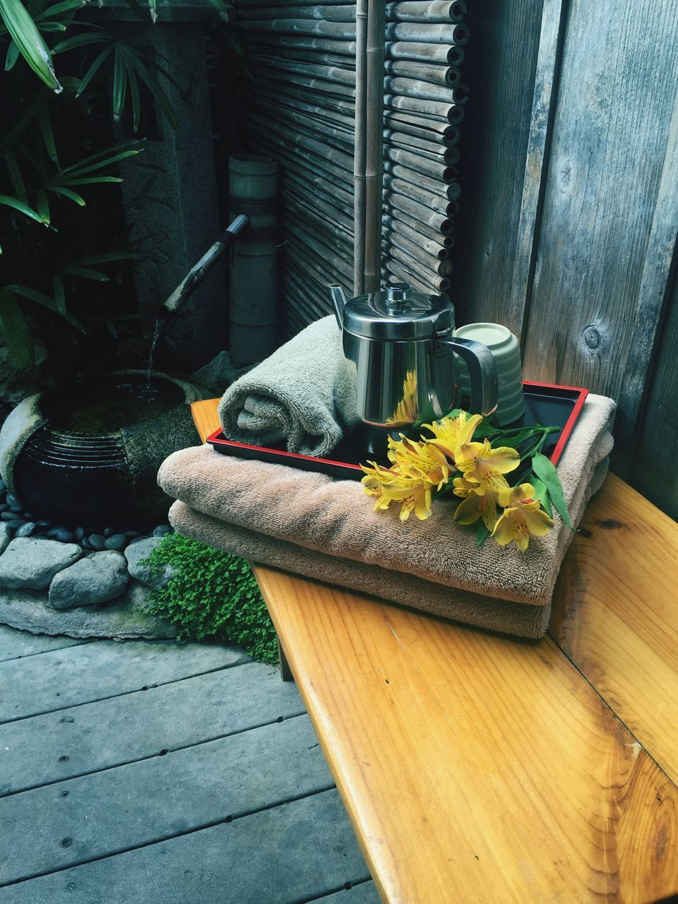 Close-Up Of Towels With Flowers And Kettle On Wood