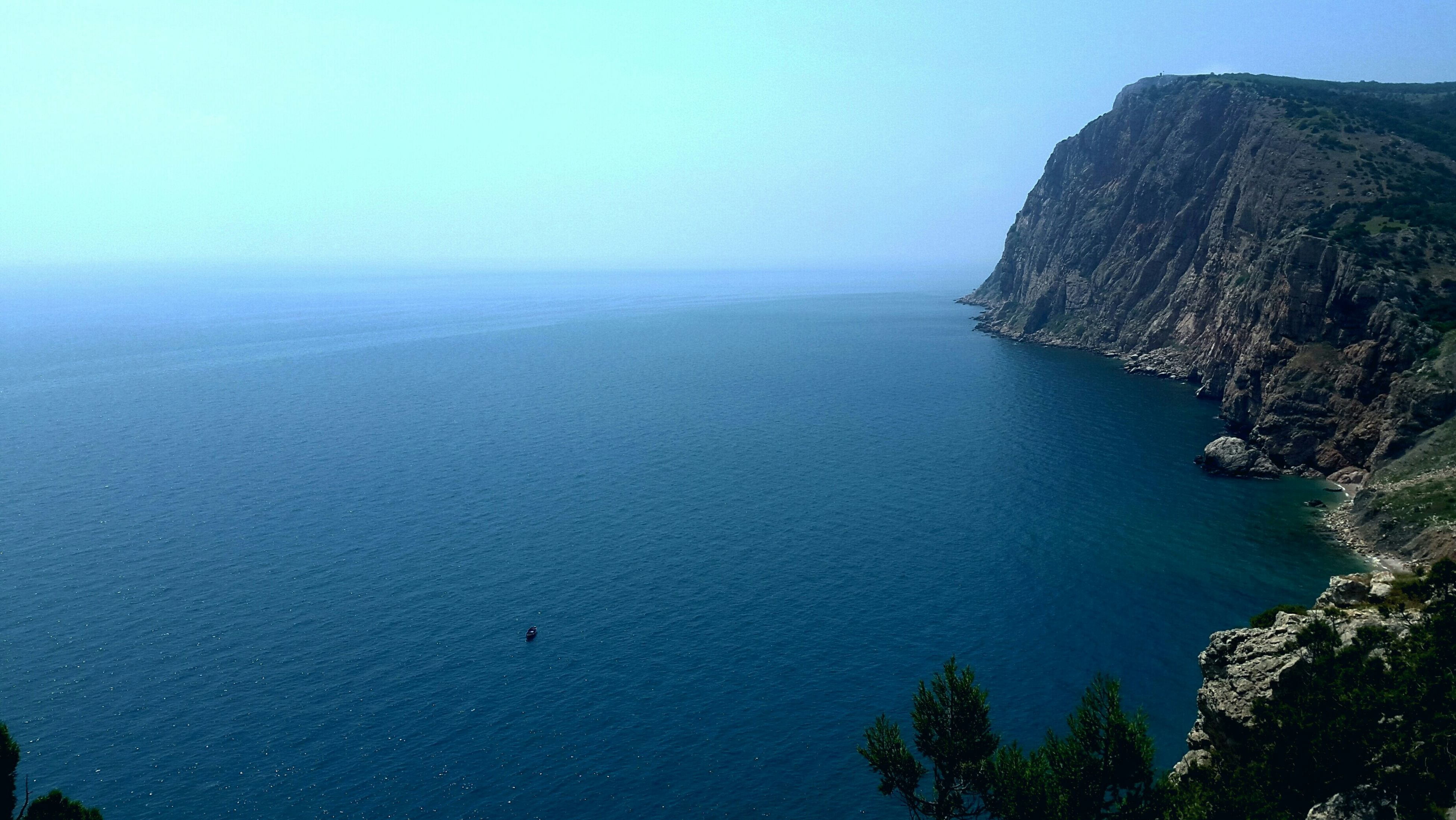 tranquil scene, scenics, tranquility, water, beauty in nature, sea, mountain, clear sky, nature, blue, idyllic, copy space, horizon over water, high angle view, mountain range, tree, non-urban scene, coastline, cliff, sky