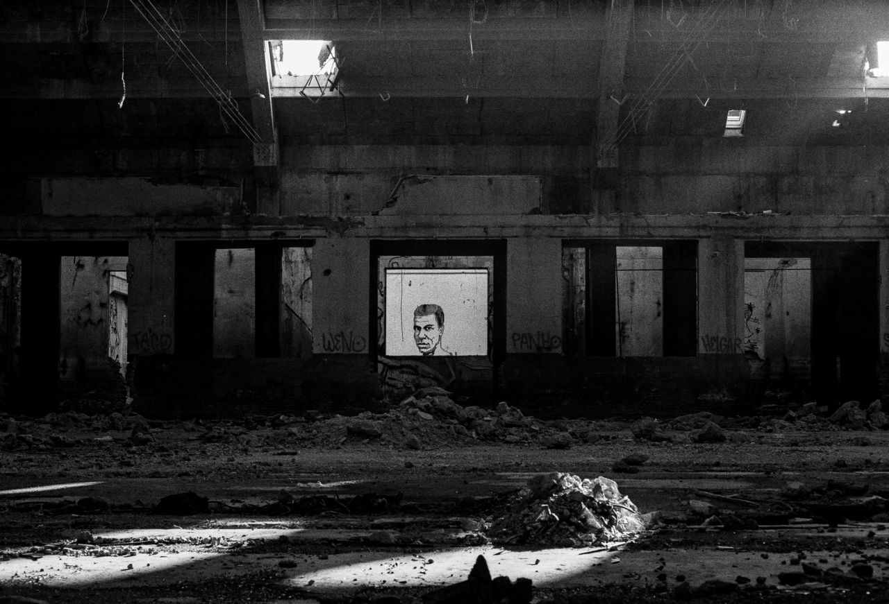 The Watcher abandoned abandoned buildings Abandoned places analog Analogue Photography Architecture art contrast Dark day grain indoors murales no people Officine Reggiane old buildings spotlight street art